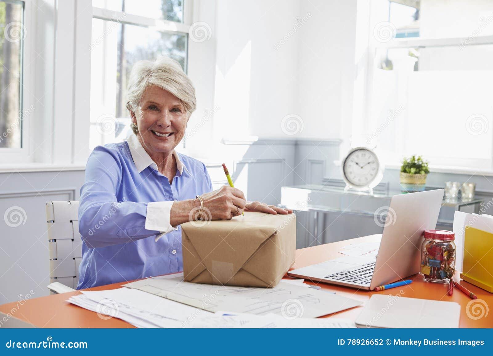 Femme supérieure à la maison adressant le paquet pour l expédition