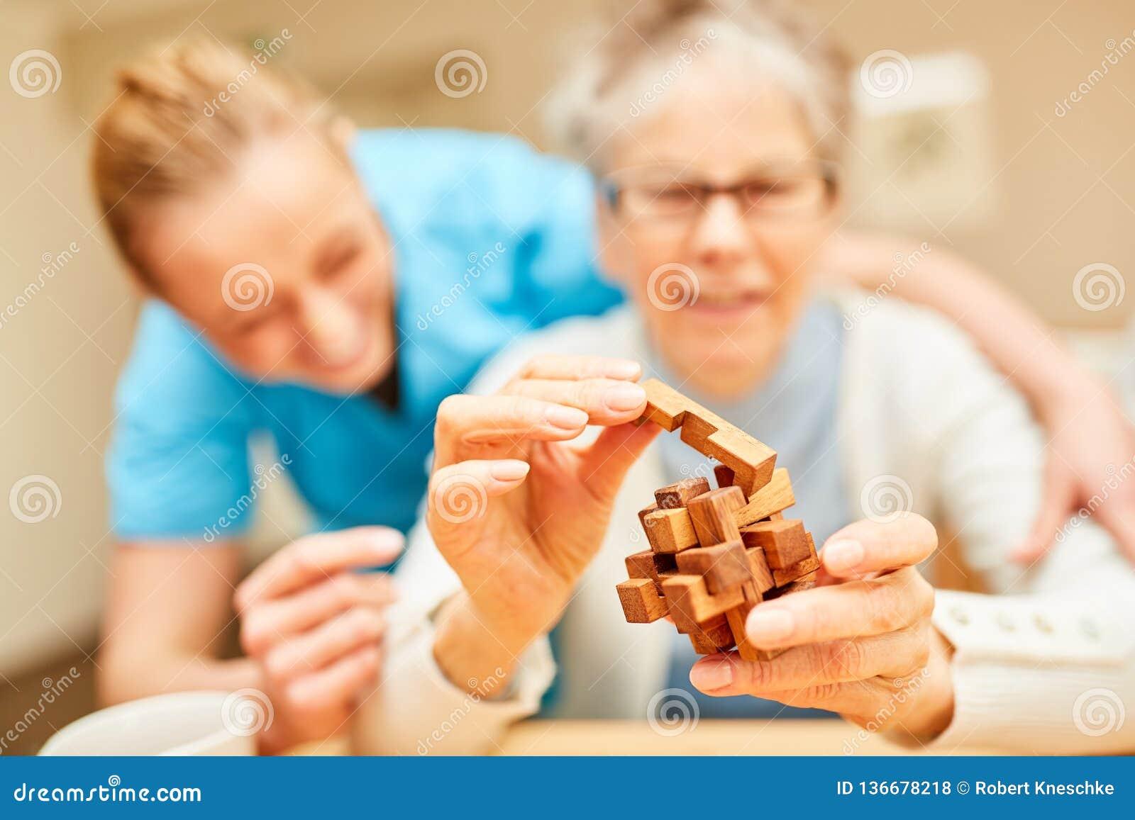 Femme supérieure avec des jeux de démence avec le puzzle en bois