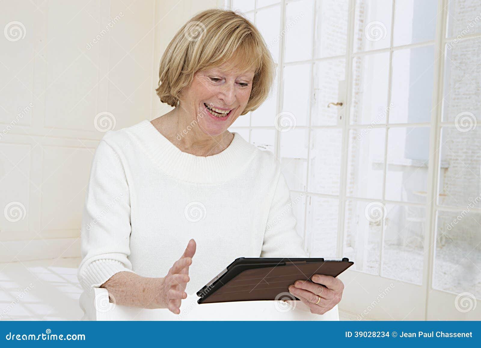 Femme supérieure avec le PC de comprimé