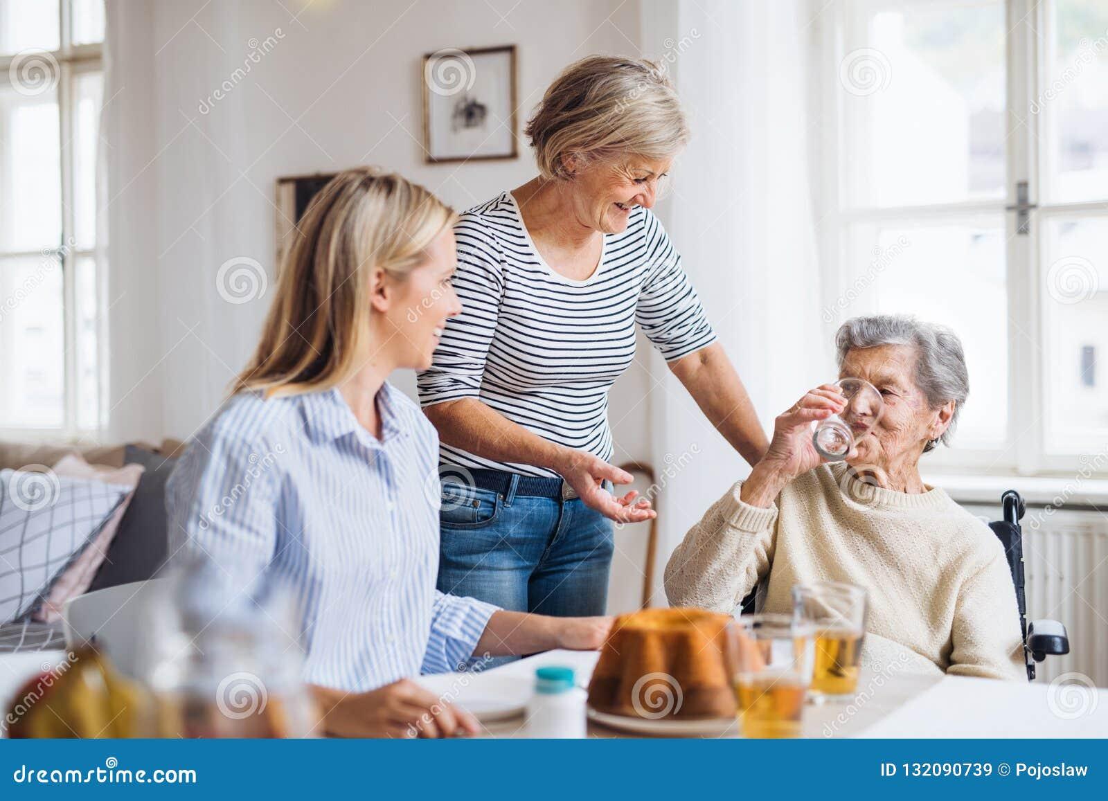 Femme supérieure dans le fauteuil roulant avec la famille s asseyant à la table à la maison, buvant