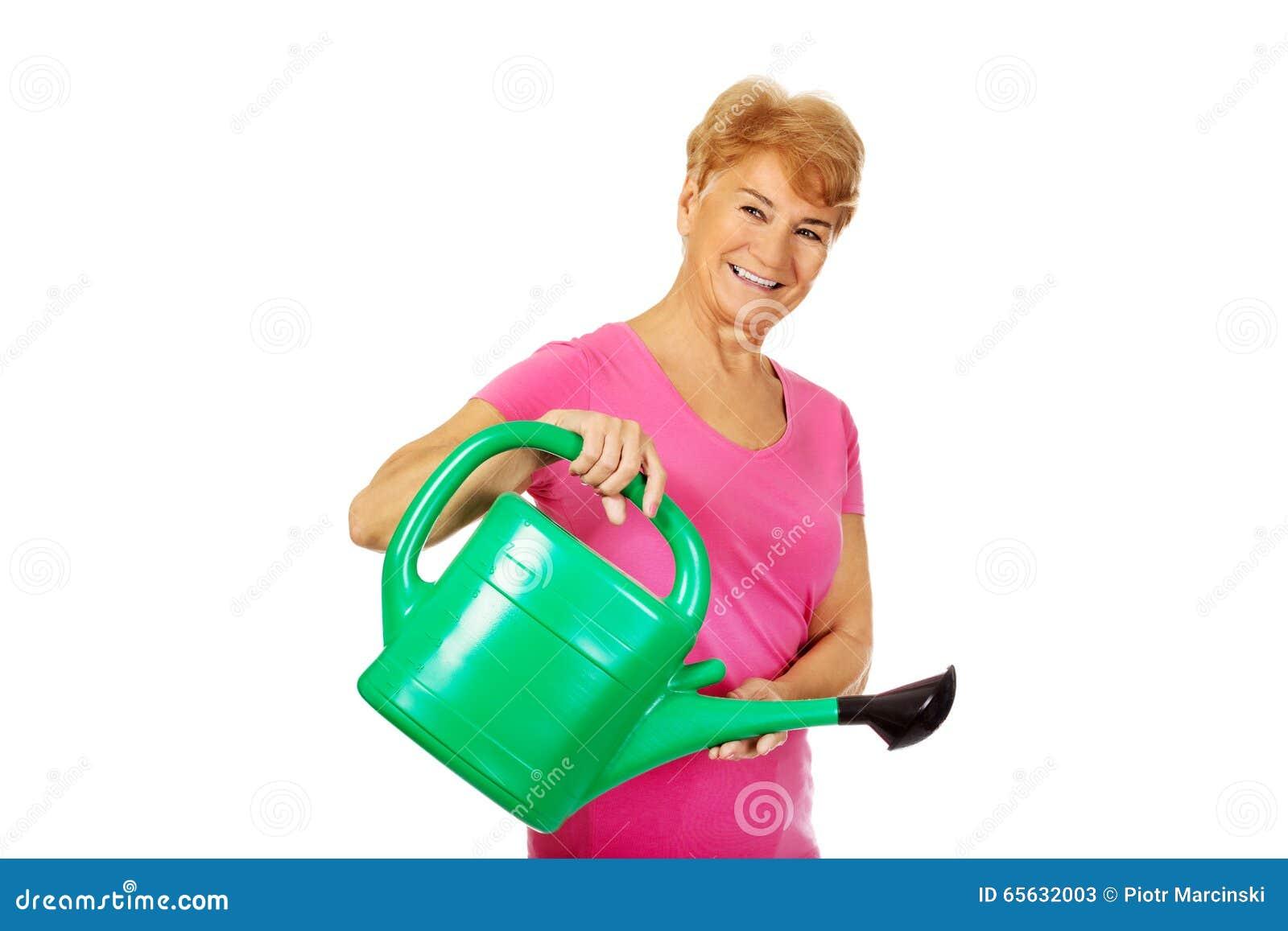 Femme supérieure de sourire avec la boîte d arrosage verte