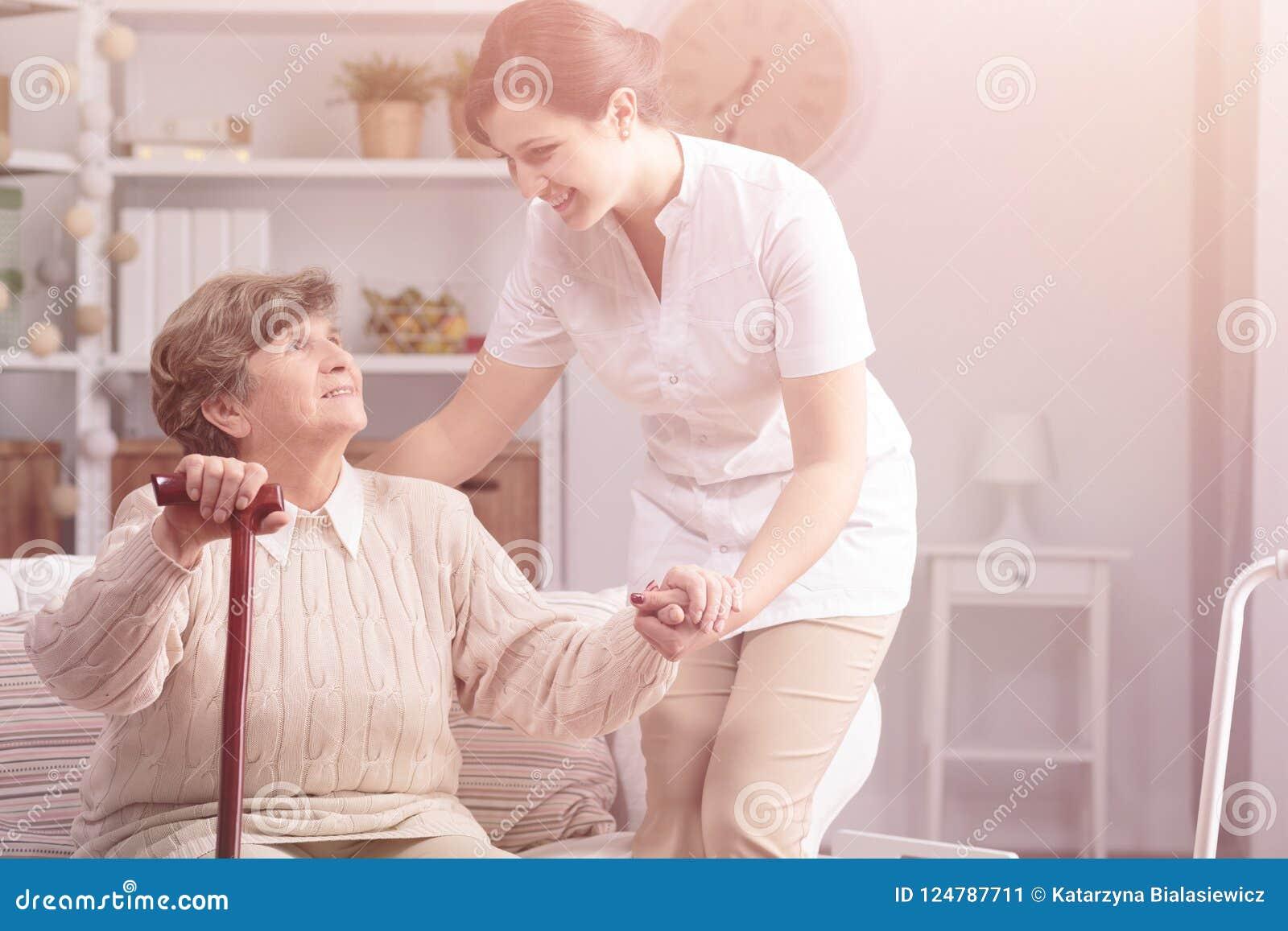 Femme supérieure de sourire de soutien de travailleur social utile avec le bâton de marche
