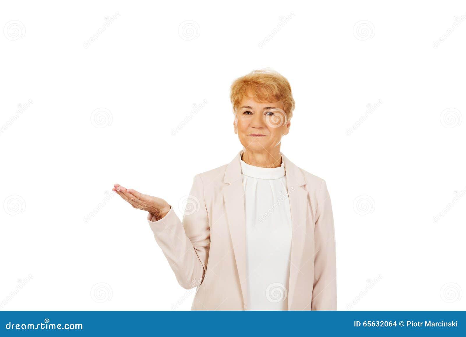 Femme supérieure de sourire tenant quelque chose sur la paume ouverte