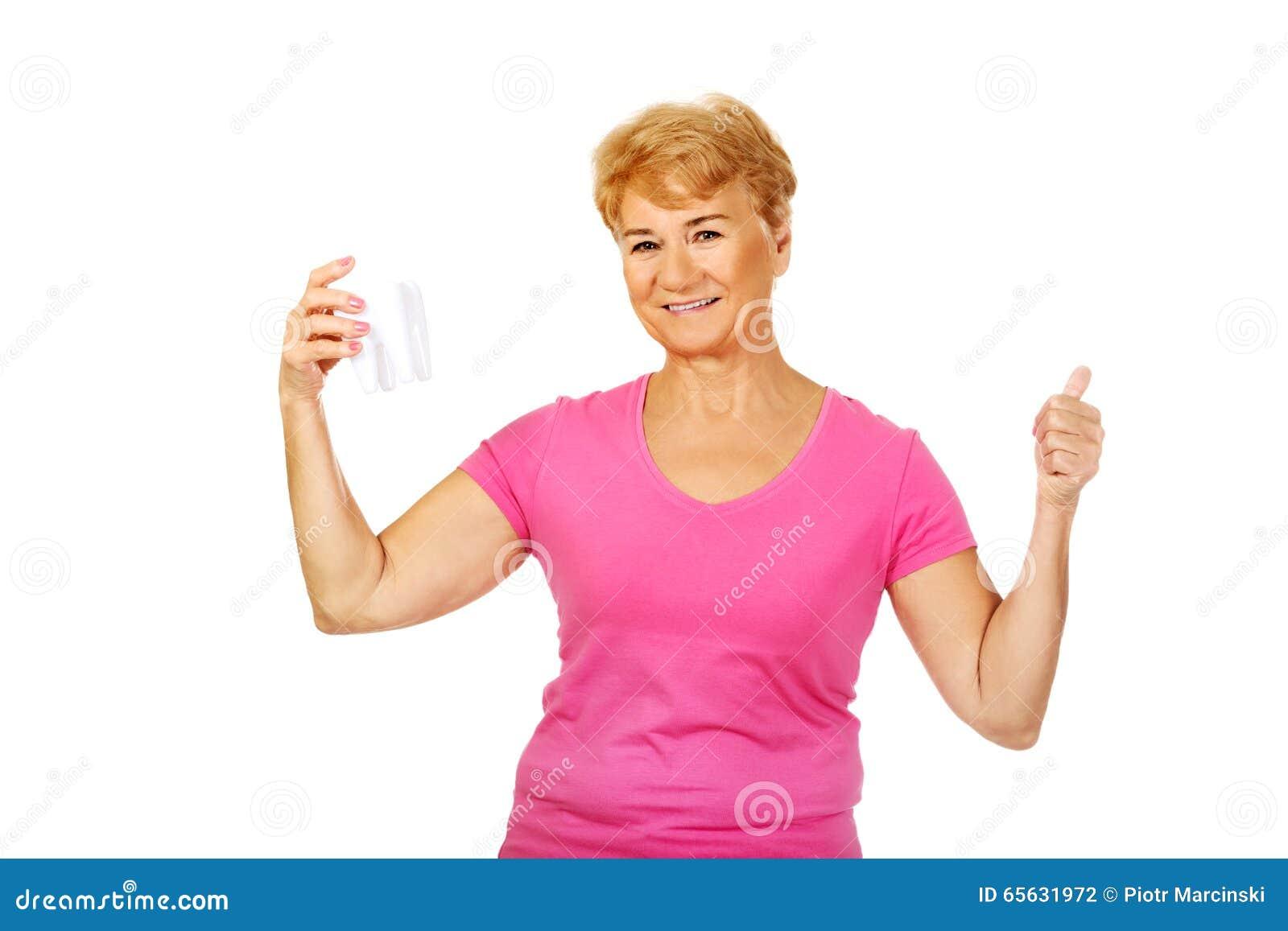 Femme supérieure de sourire tenant un modèle de dent et montrant le pouce