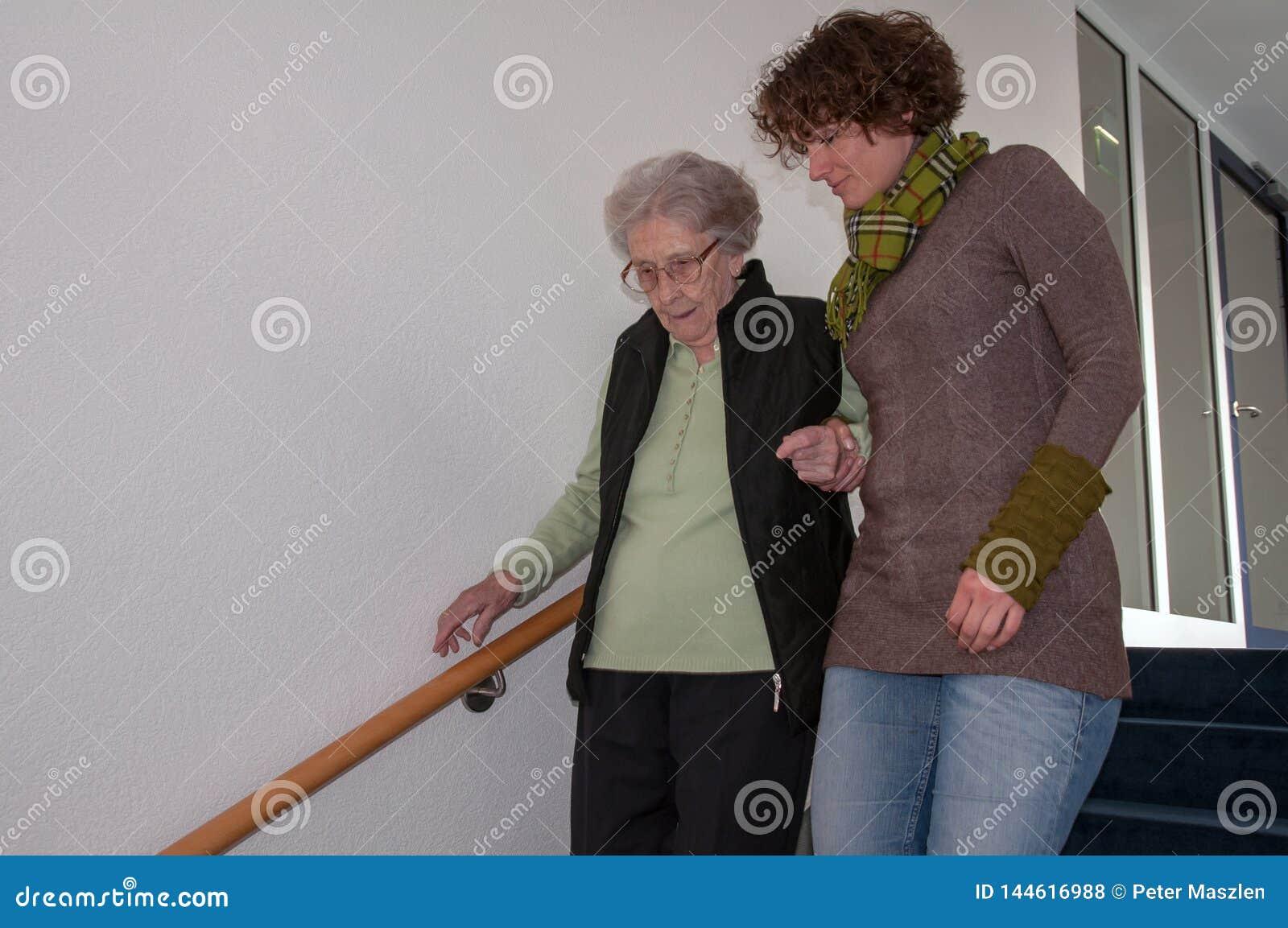 Femme supérieure descendant des escaliers avec des coups de main de jeune femme