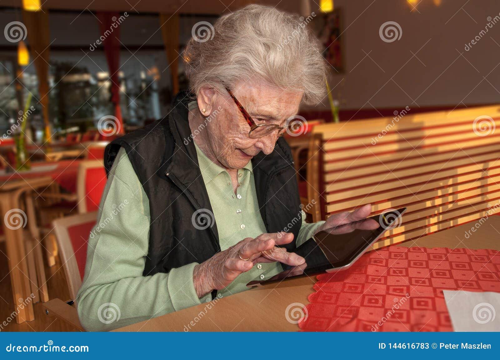 Femme supérieure essayant de manipuler la tablette