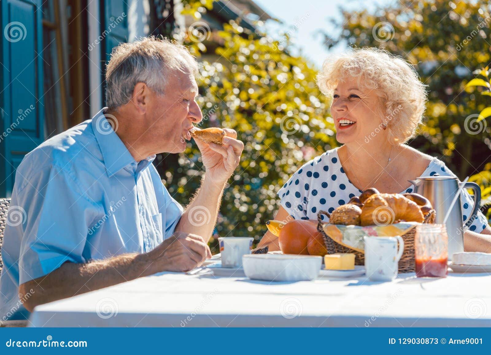 Femme supérieure et homme prenant le petit déjeuner se reposant dans leur jardin dehors