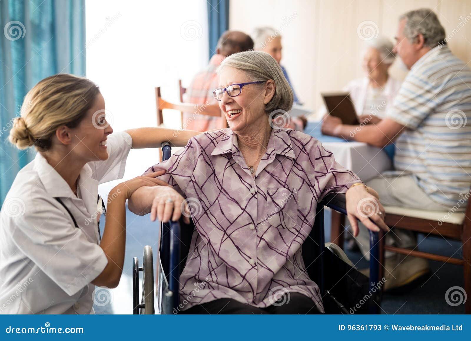 Femme supérieure handicapée gaie s asseyant sur le fauteuil roulant regardant le docteur féminin