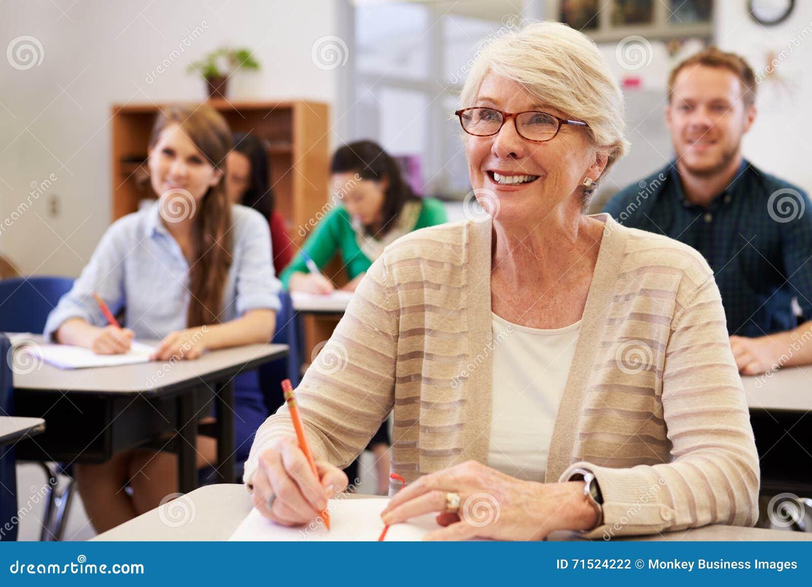 Femme supérieure heureuse à une classe d éducation des adultes recherchant