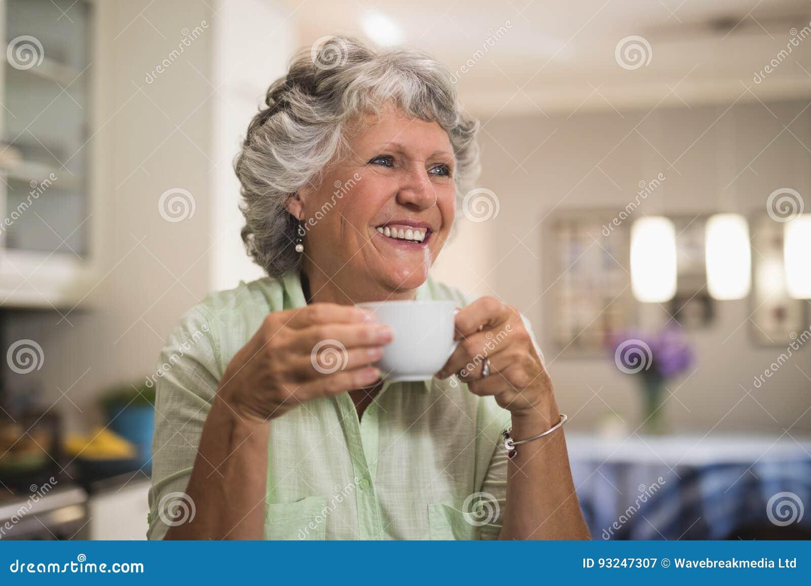 Femme supérieure heureuse tenant la tasse à la maison