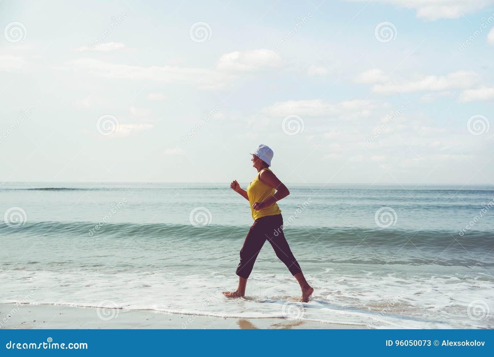 Femme supérieure pulsant sur la plage de mer