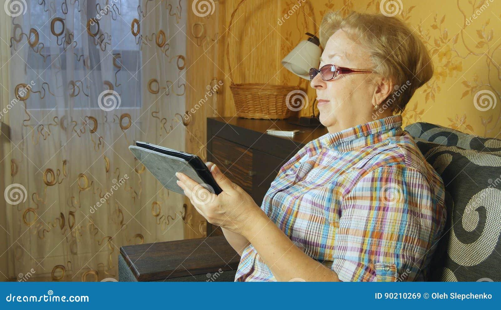 Femme supérieure s asseyant dans le sofa avec le comprimé électronique