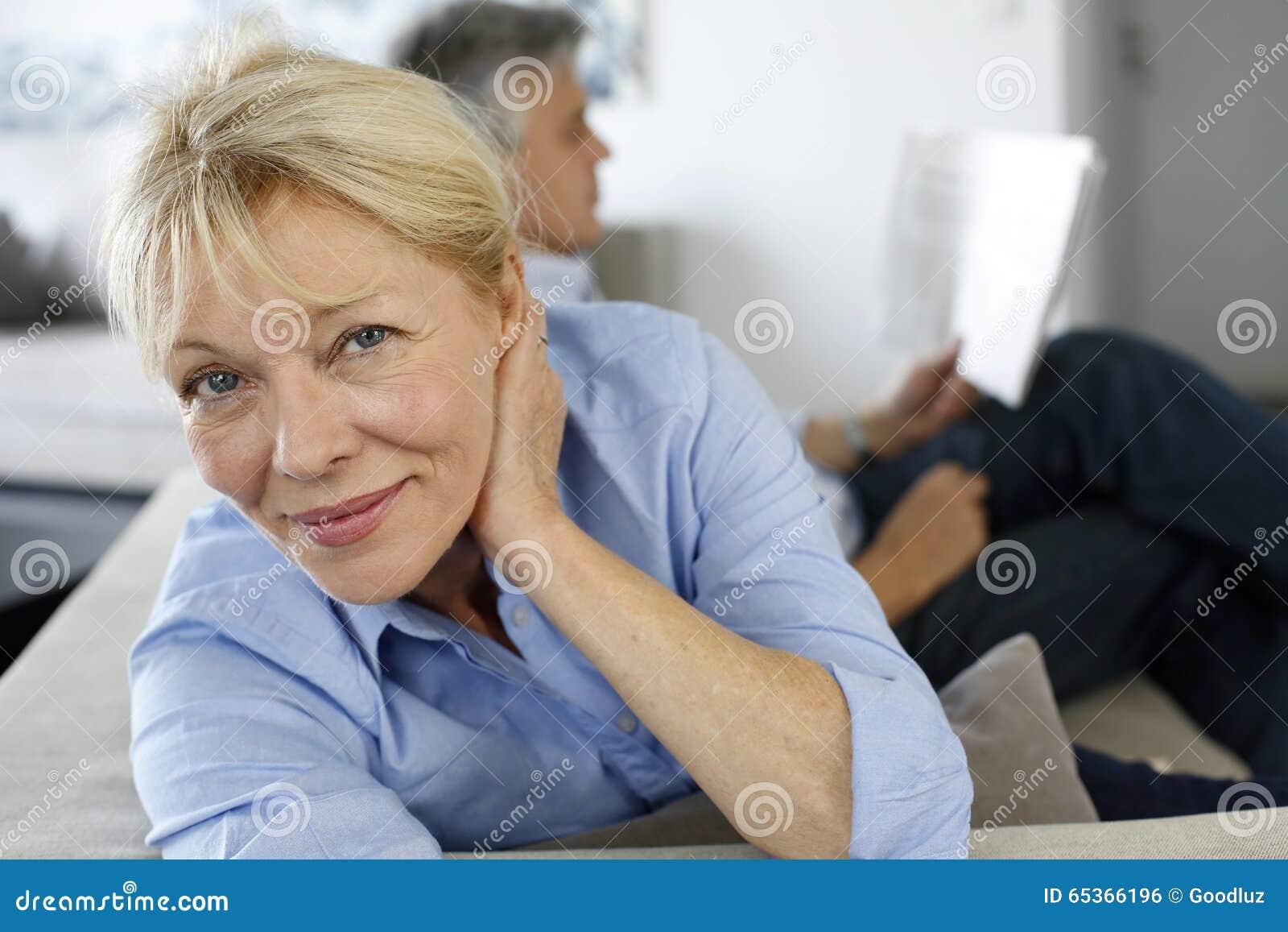 Femme supérieure s asseyant sur le sofa