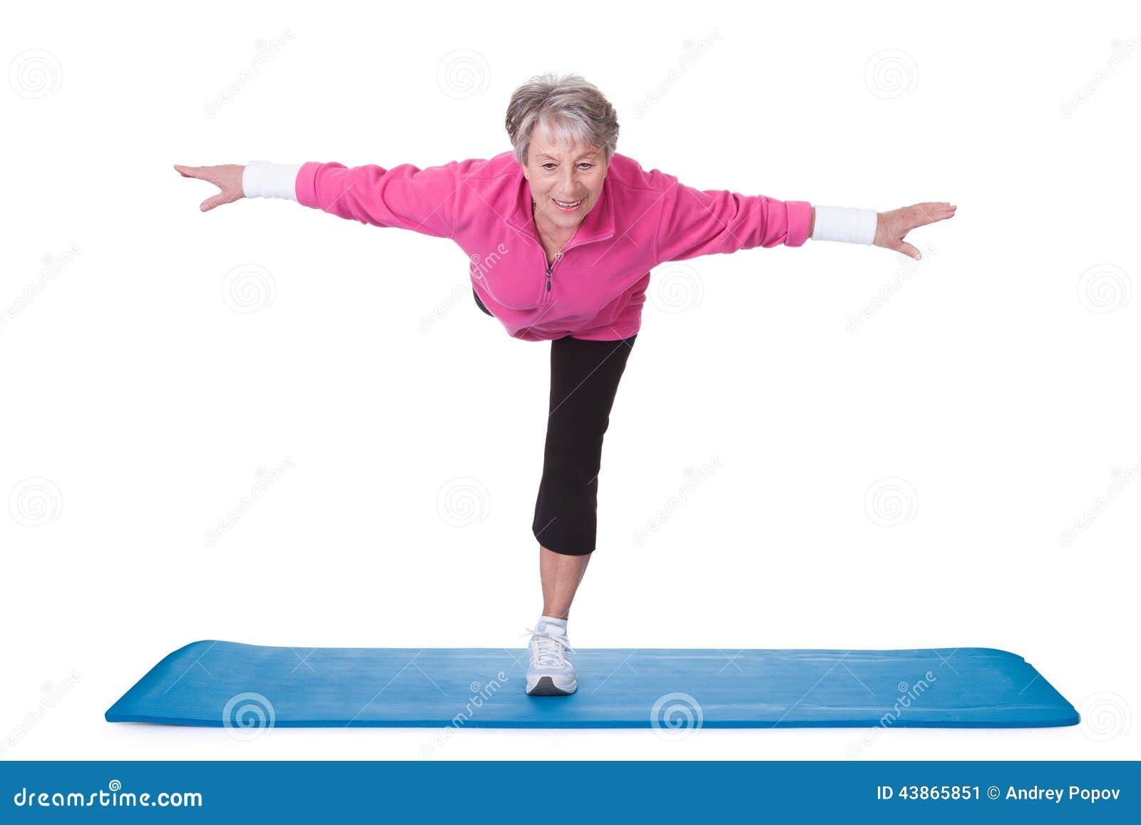 Femme supérieure se tenant sur un jambe et exercice