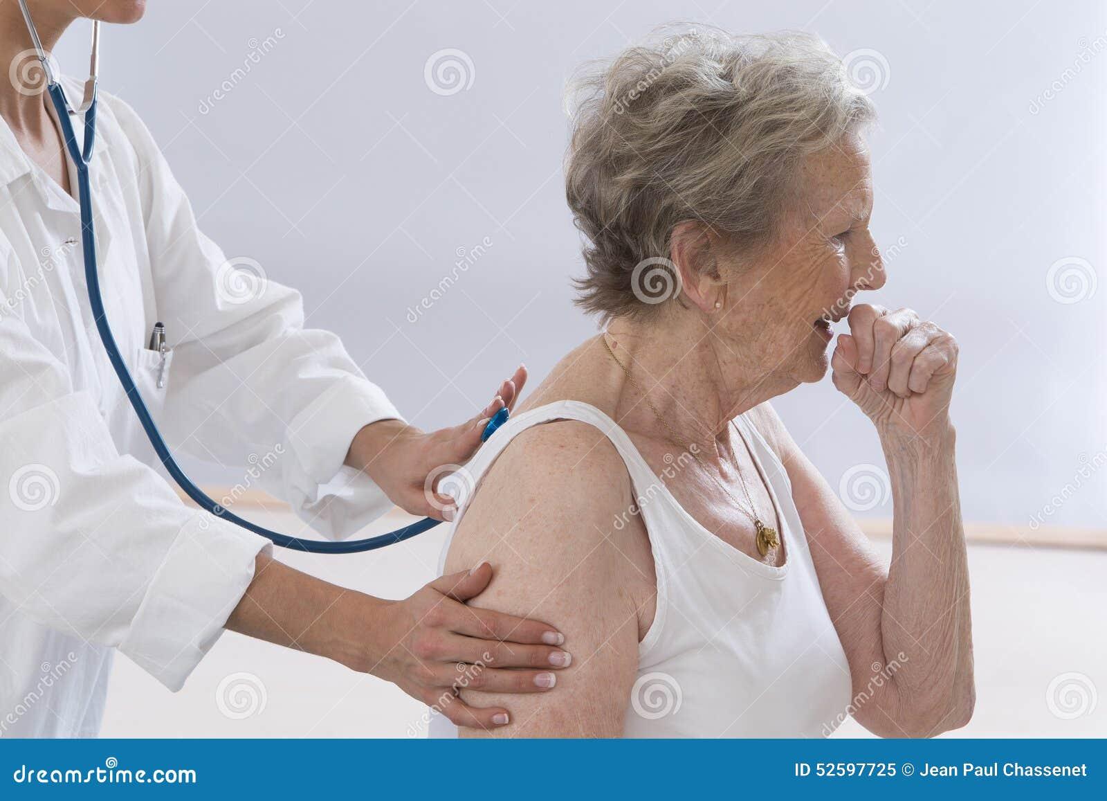 Femme supérieure toussant tandis que docteur Examining Her
