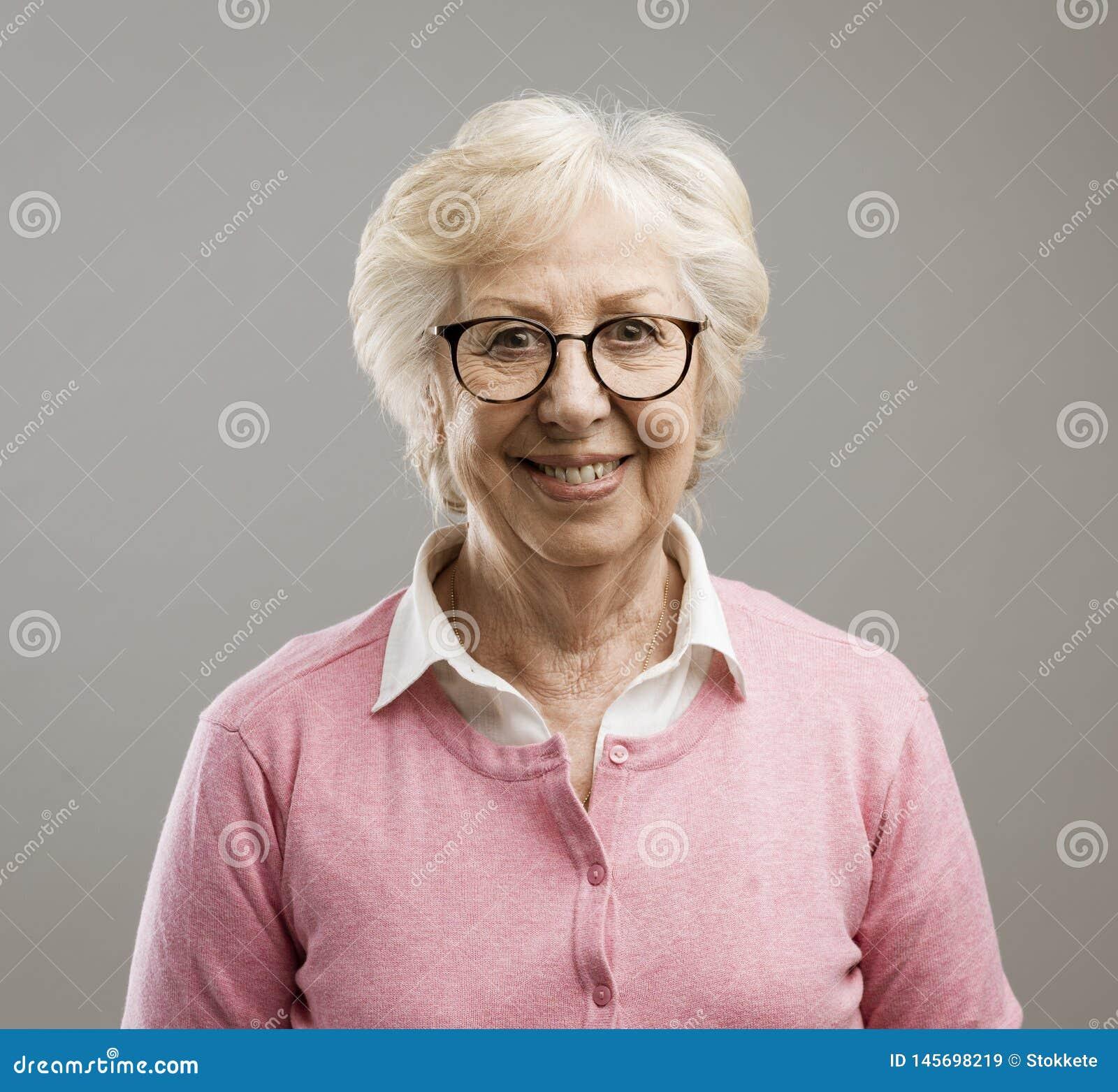 Femme sup?rieure heureuse posant sur le fond gris