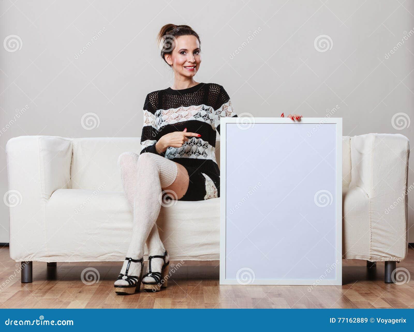 Femme sur le sofa tenant le conseil de présentation vide
