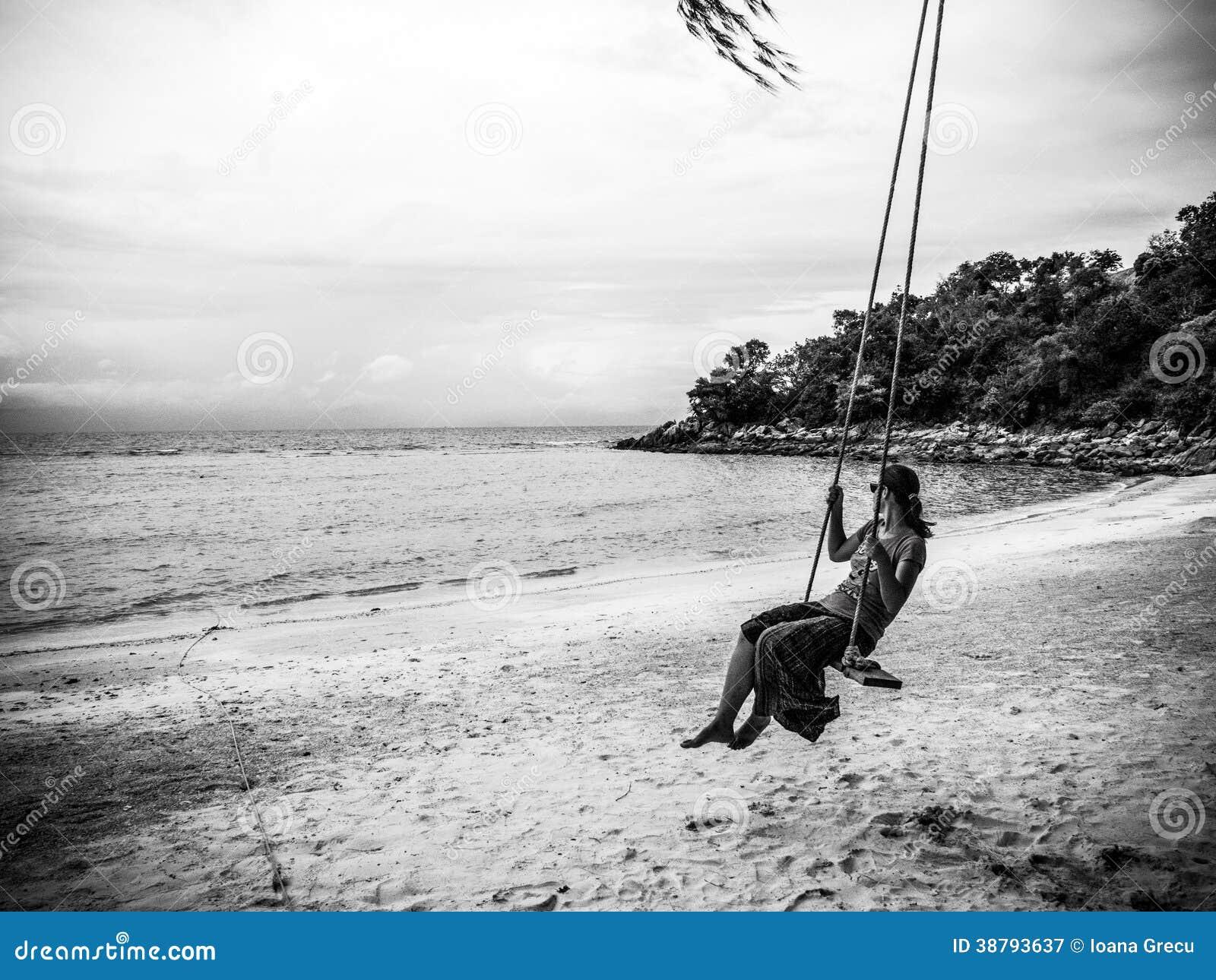 Femme sur une oscillation à une plage tropicale