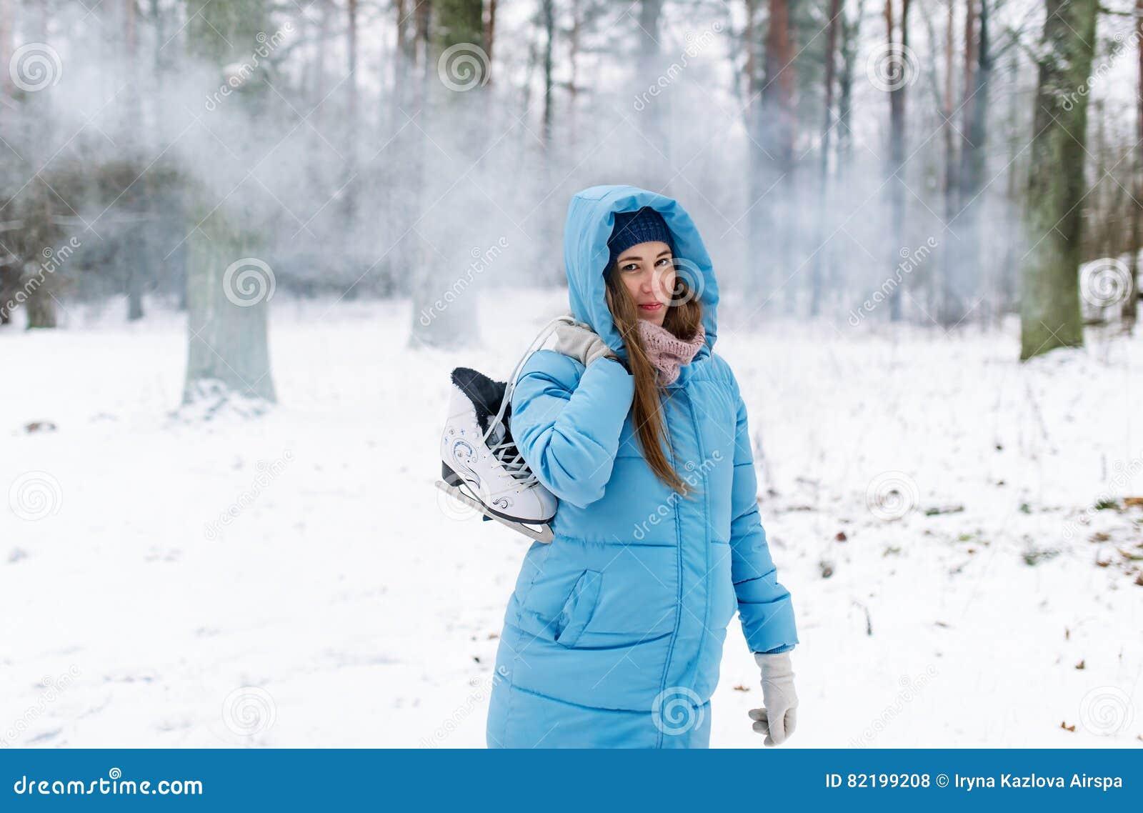Femme tenant des patins de glace dehors dans la neige
