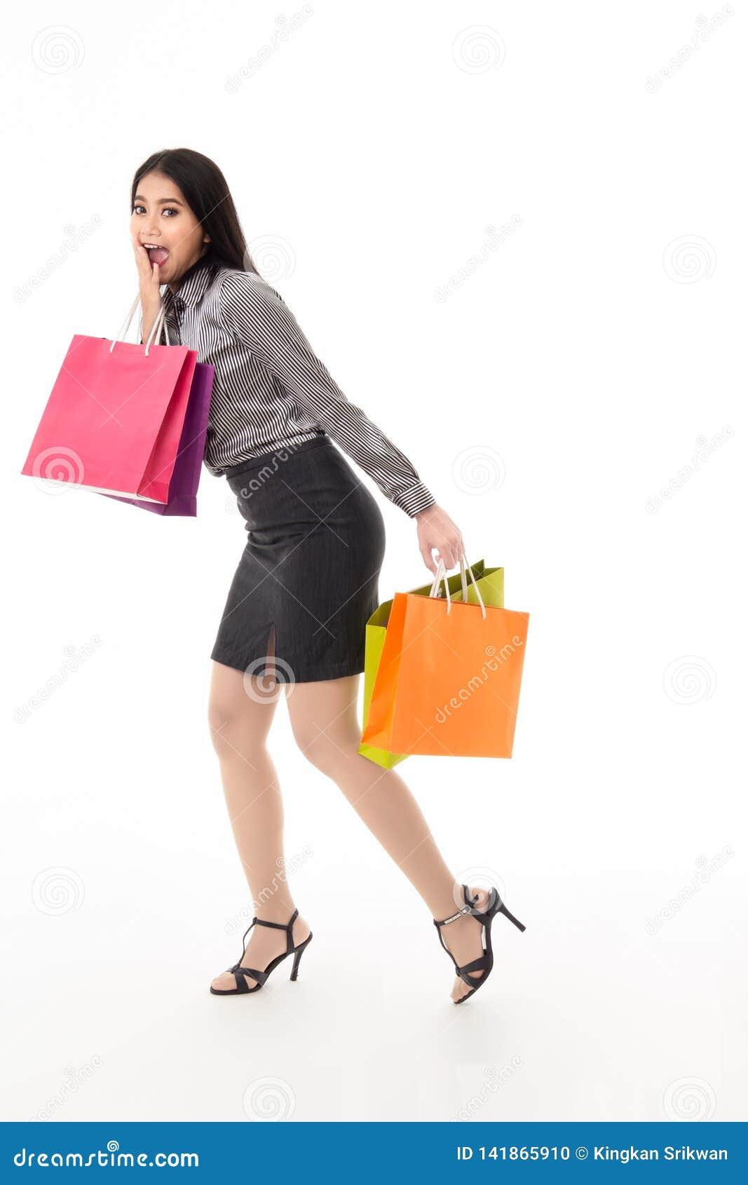 Femme tenant des sacs à provisions avec le bavardage et l expression étonnante de visage