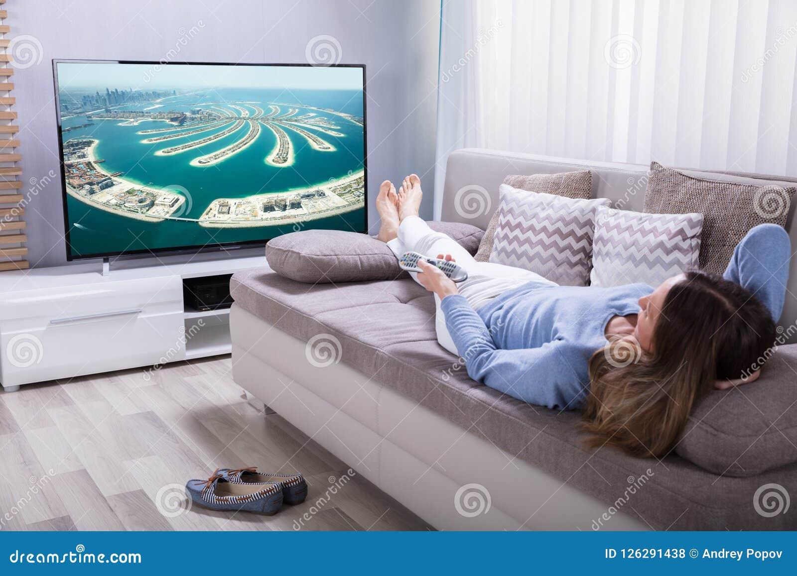Femme tenant la calculatrice tout en regardant la télévision