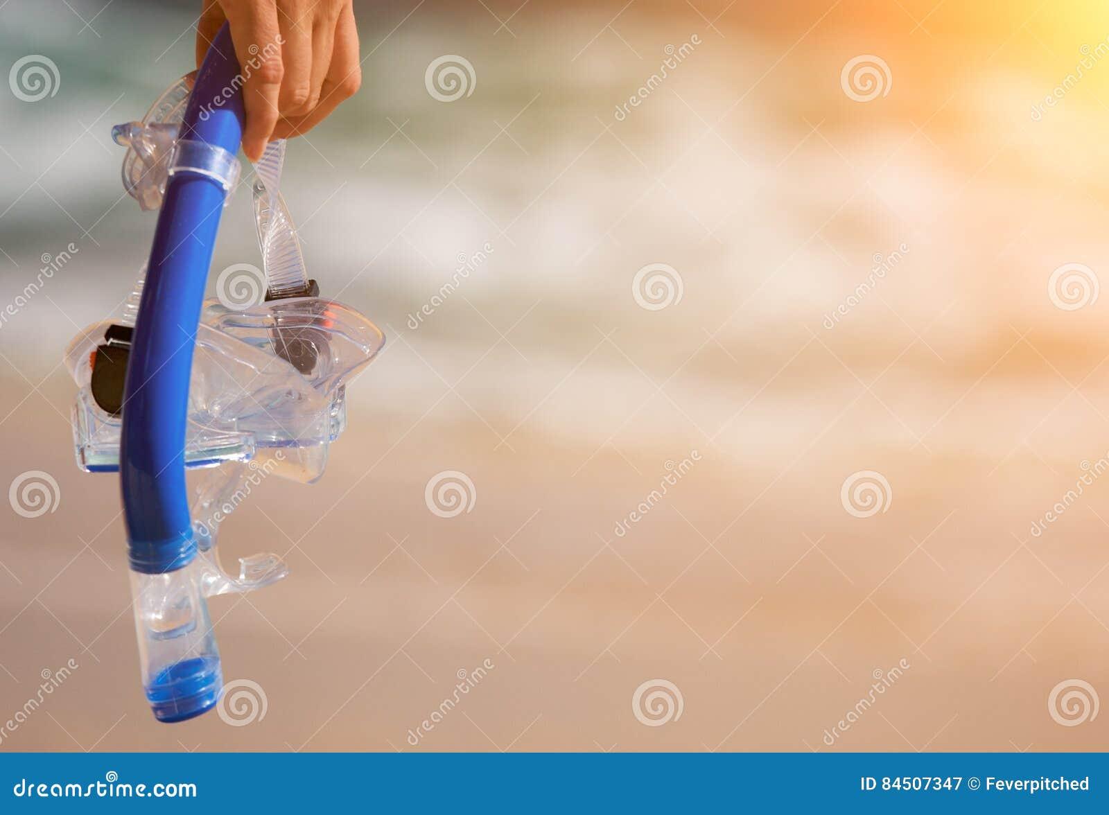 Femme tenant la vitesse naviguante au schnorchel sur la plage au coucher du soleil