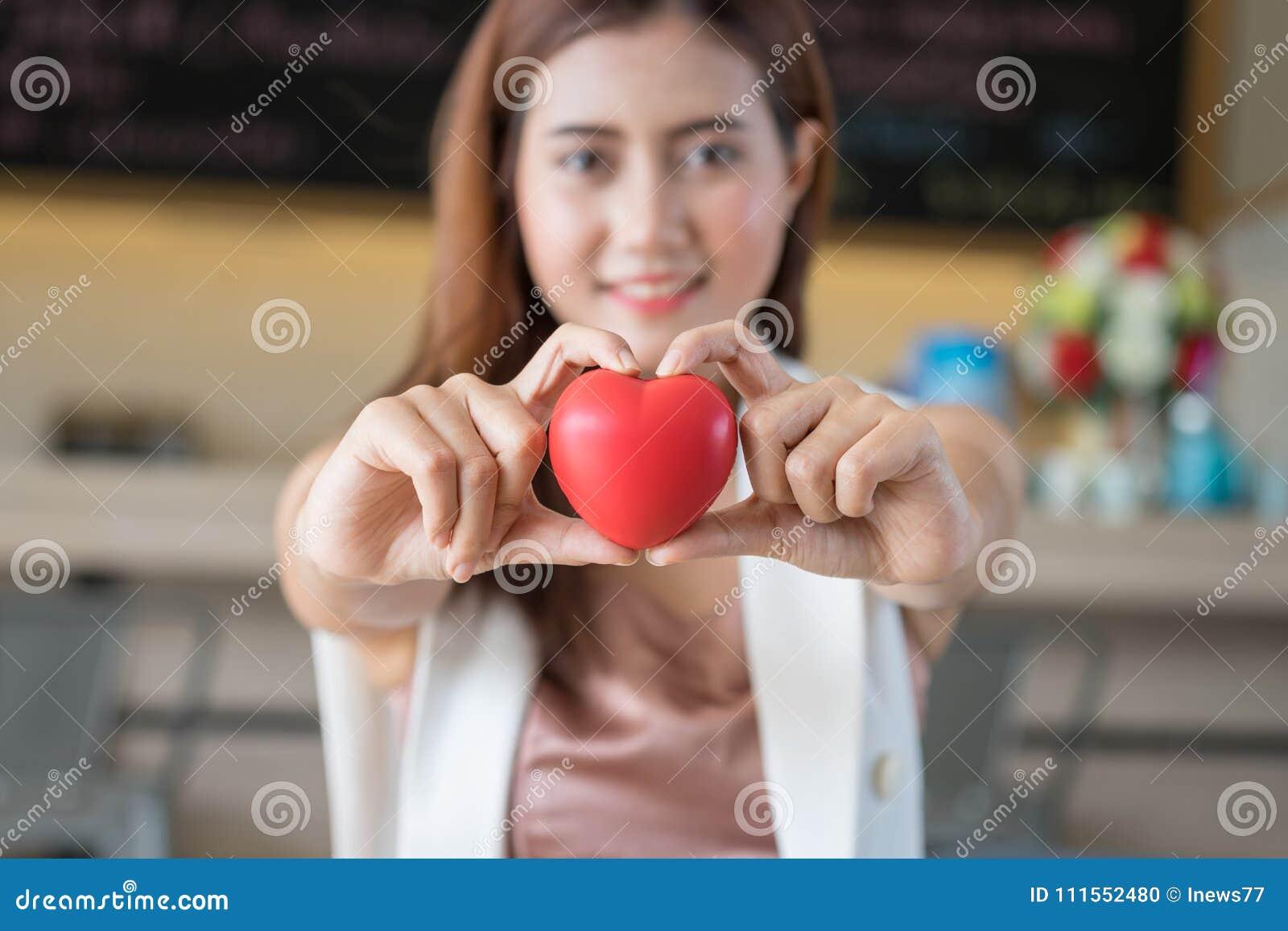 Femme tenant le coeur rouge dans des mains