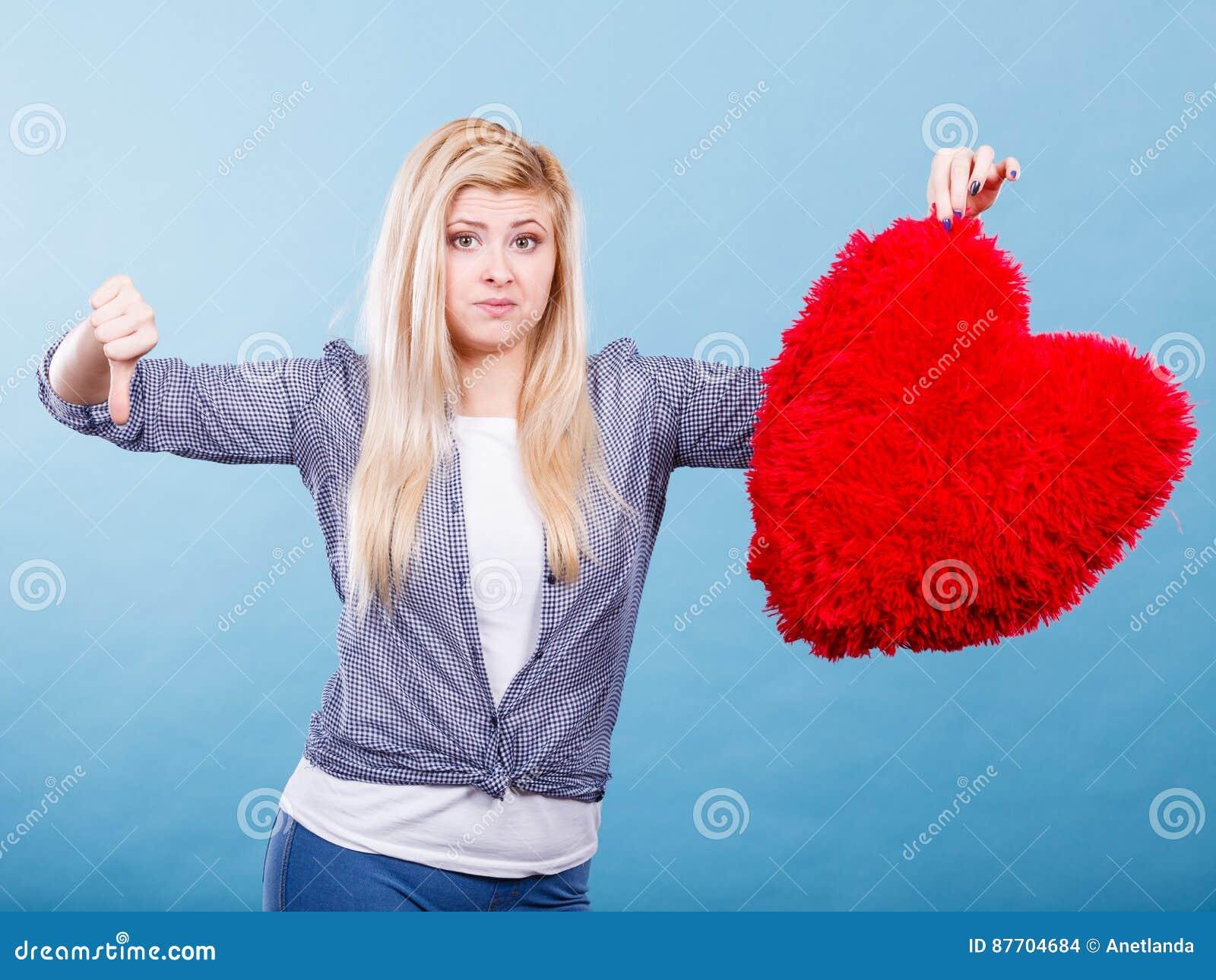Femme tenant le coeur rouge montrant le pouce vers le bas
