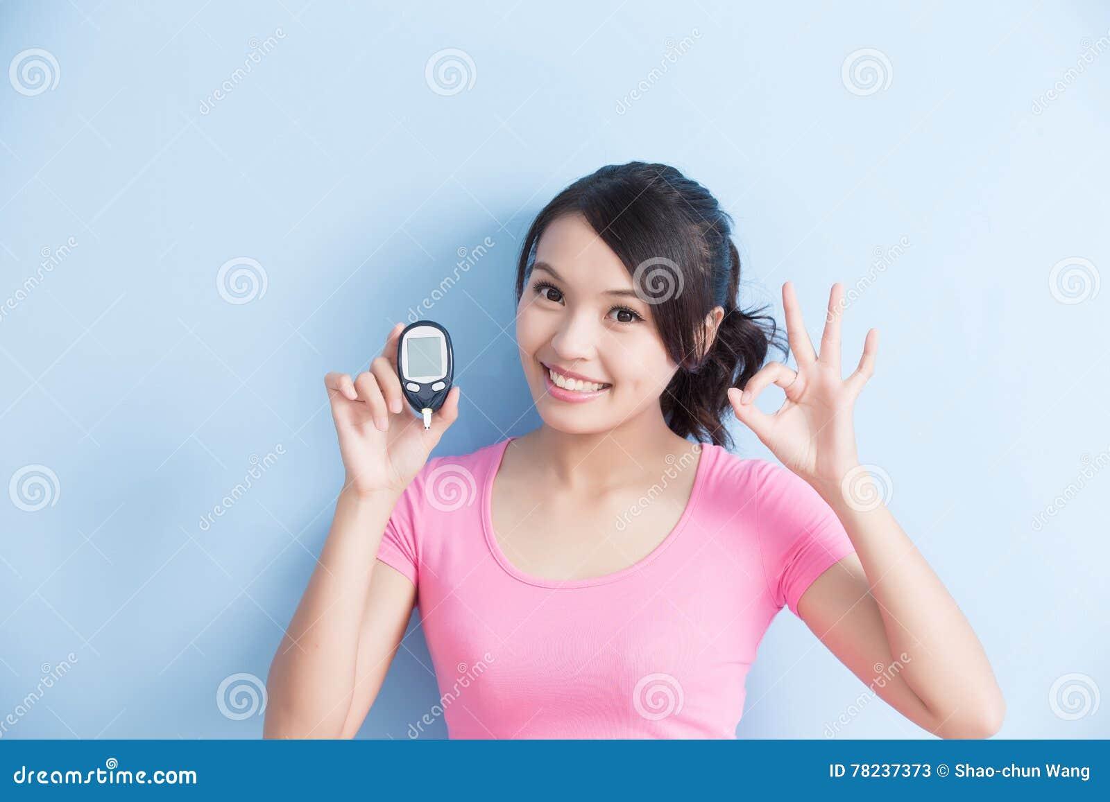 Femme tenant le mètre de glucose sanguin