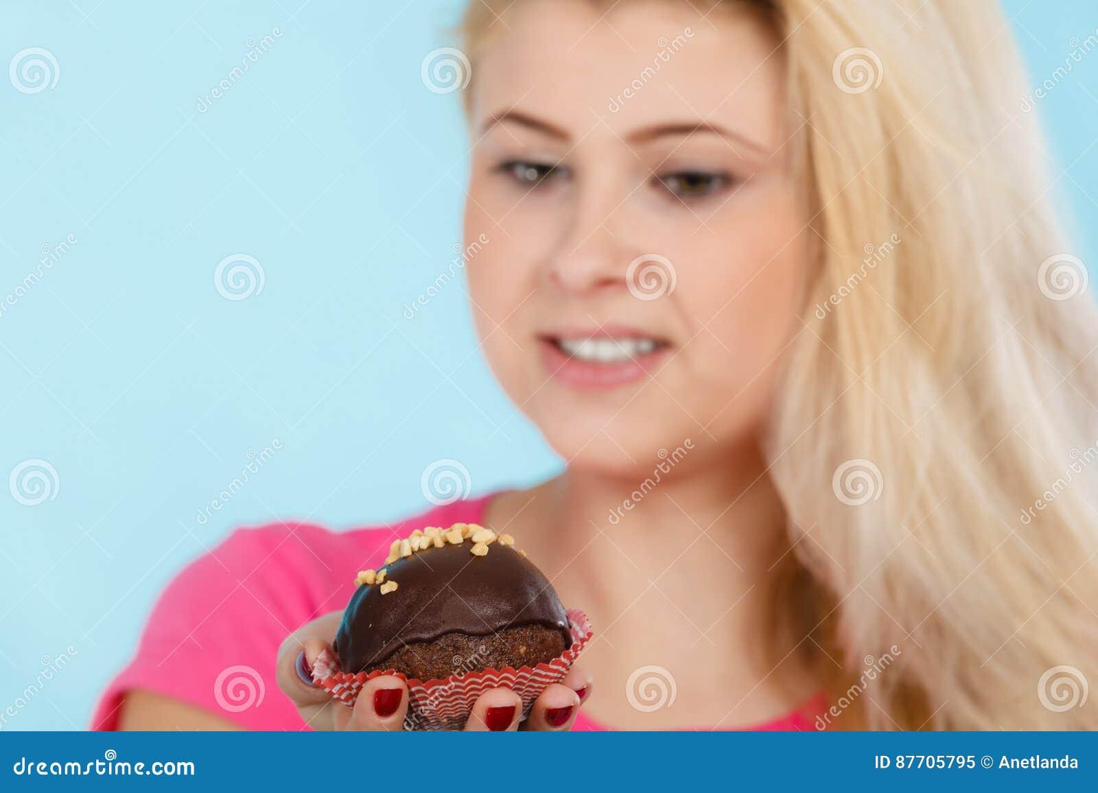 Femme tenant le petit gâteau de chocolat environ sur la morsure