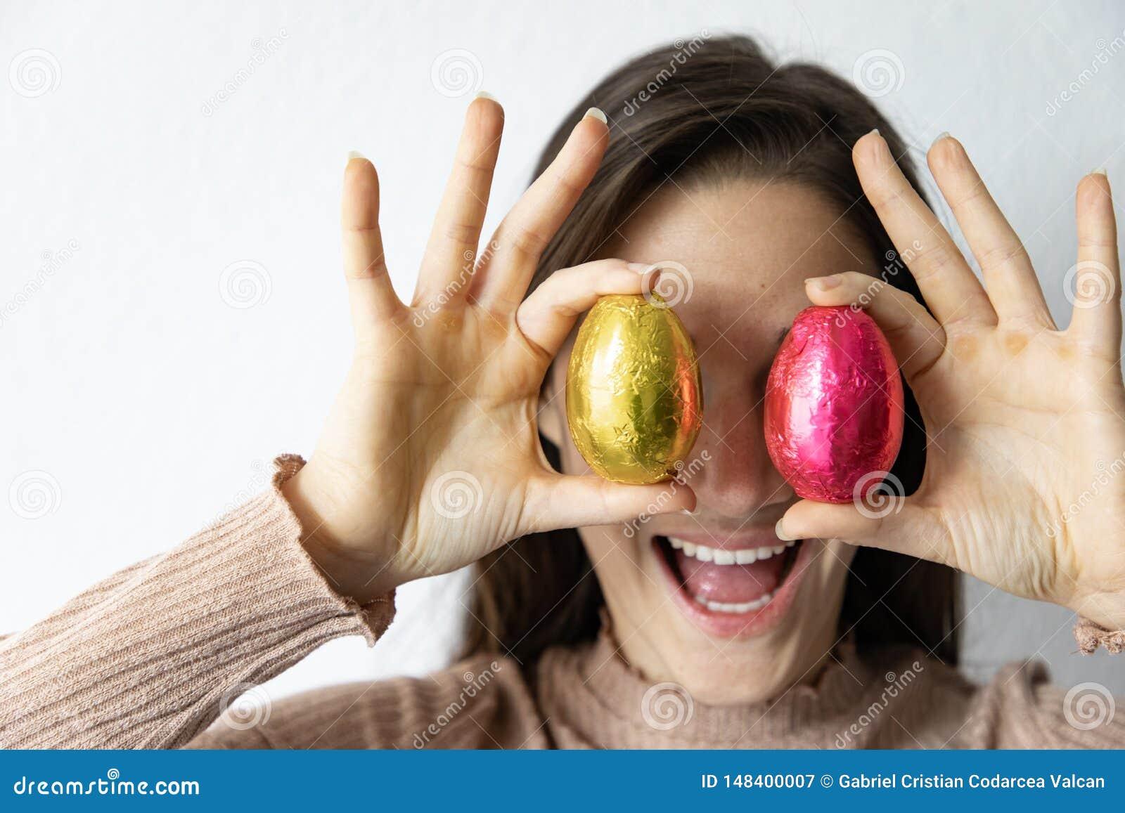 Femme tenant les oeufs de p?ques bleus et rouges de chocolat devant ses yeux