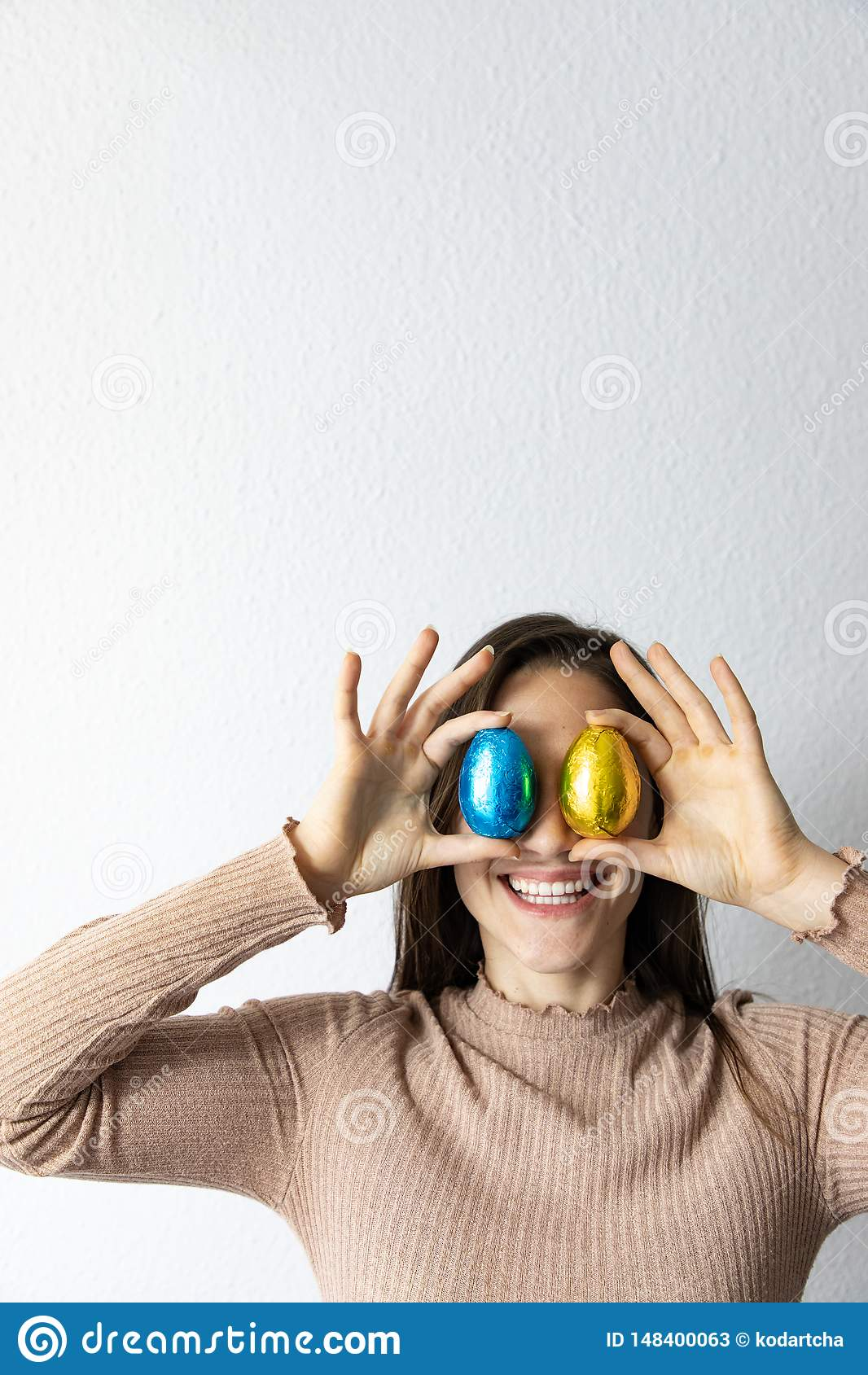 Femme tenant les oeufs de p?ques bleus et d or de chocolat devant ses yeux