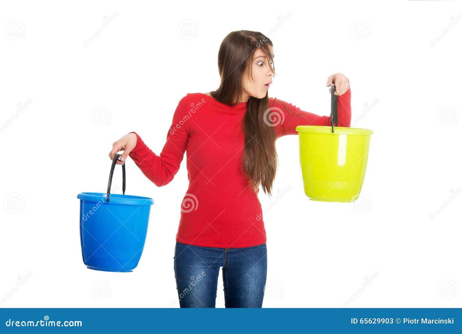 Femme tenant les seaux en plastique vides