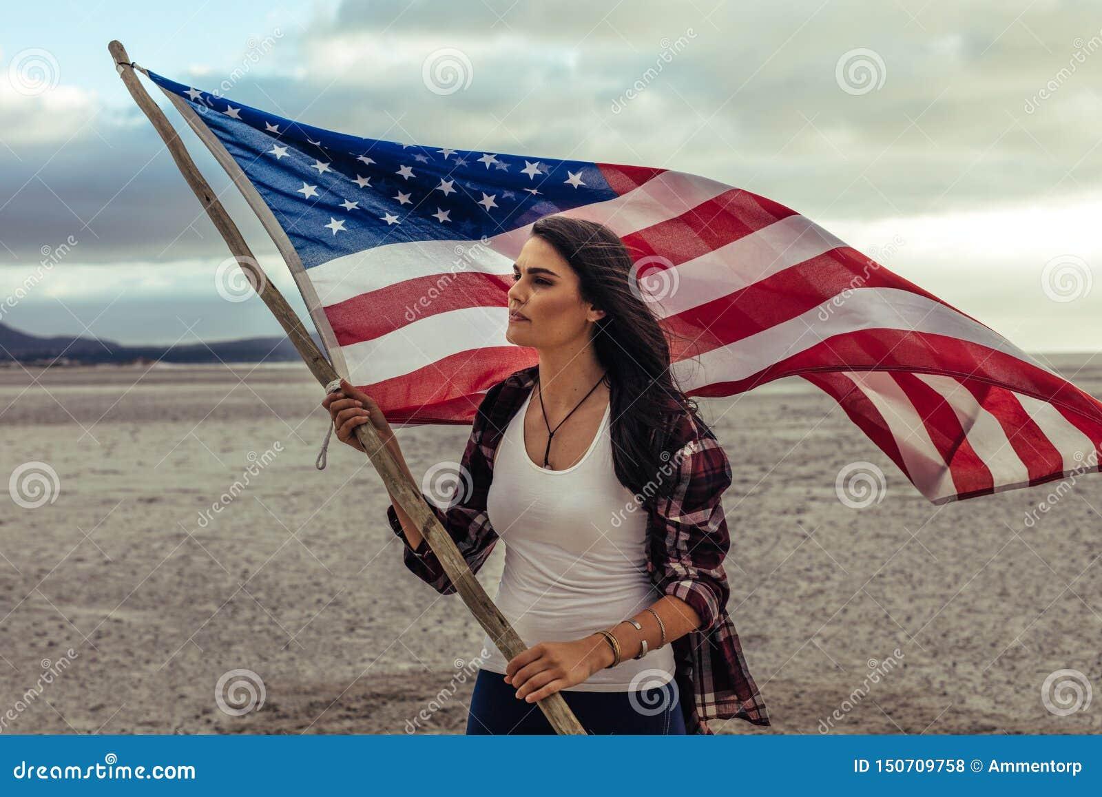 Femme tenant un drapeau des Etats-Unis sur la plage