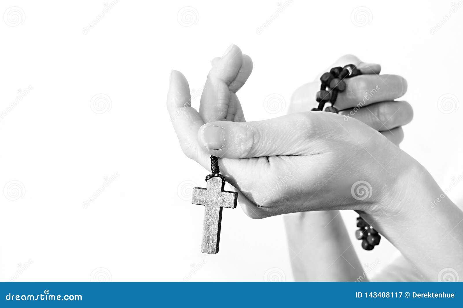 Femme tenant une croix avec des perles de chapelet