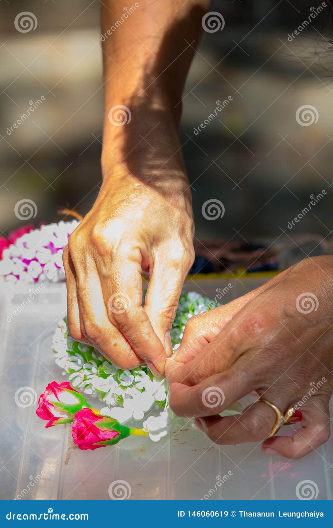 Femme tha?landaise faisant ? une tradition la guirlande tha?landaise de fleurs