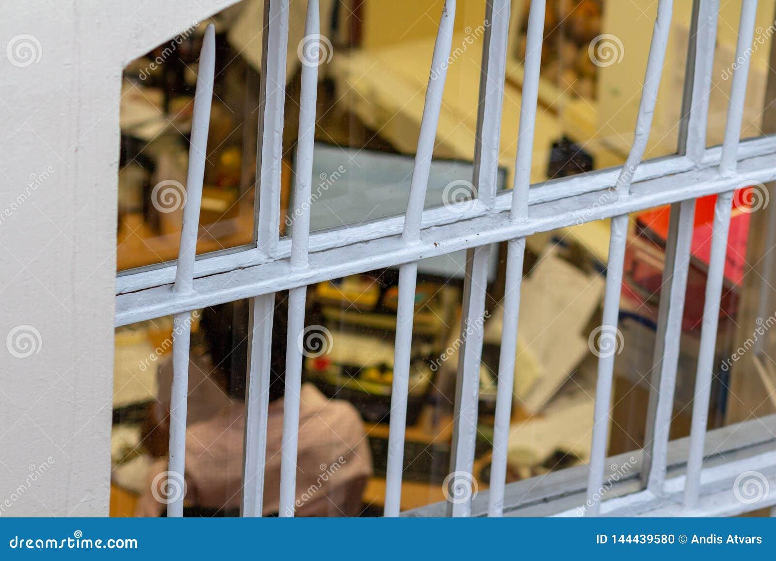 Femme travaillant à la vue de bureau par des grilles Les gens sont soumis à une contrainte parce qu ils sont emprisonnés en heure
