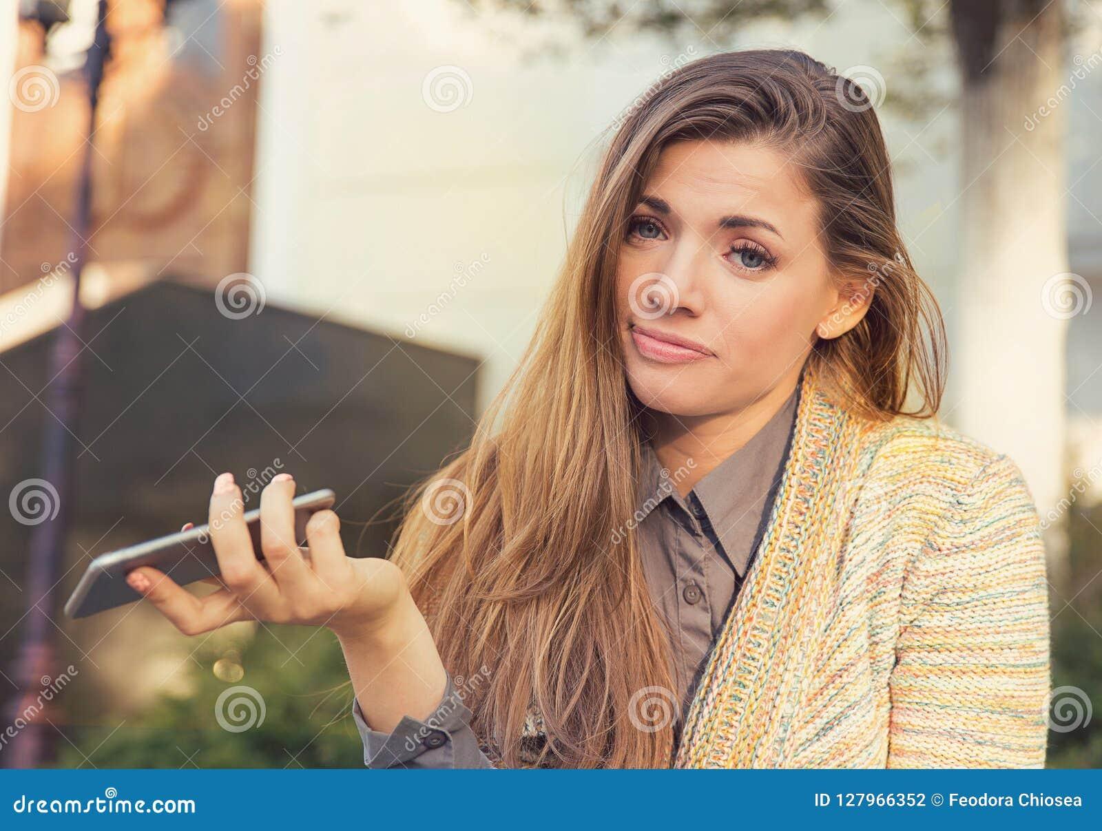 Femme triste contrariée avec l extérieur debout de téléphone portable dans la rue