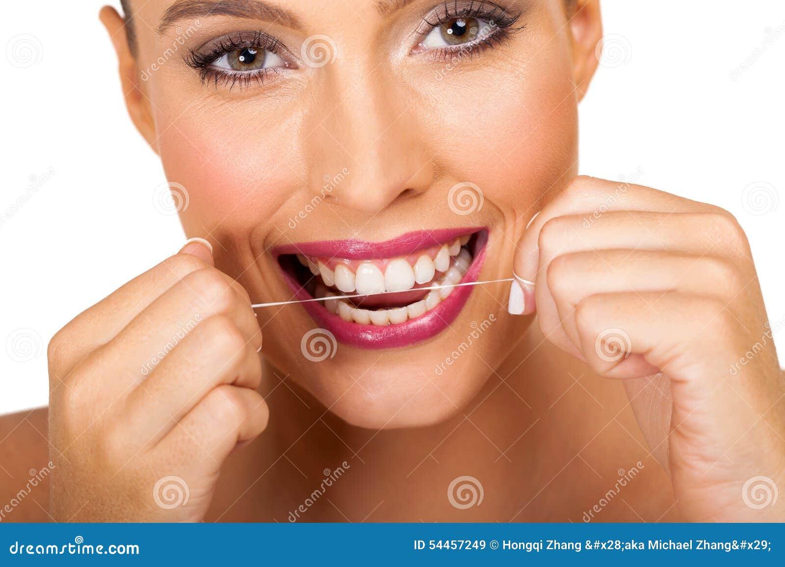 Femme utilisant la soie dentaire