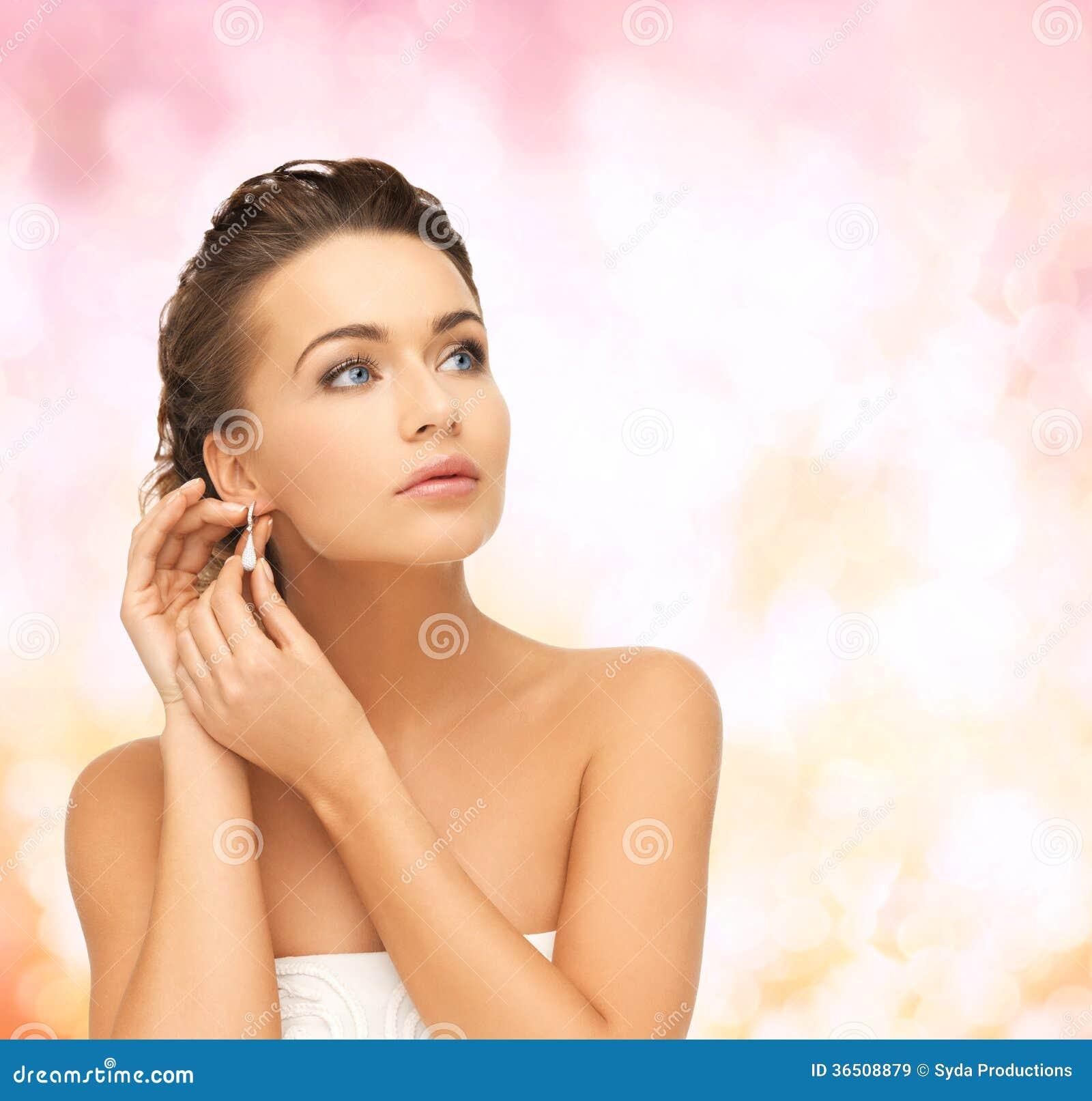 Femme utilisant les boucles d oreille brillantes de diamant