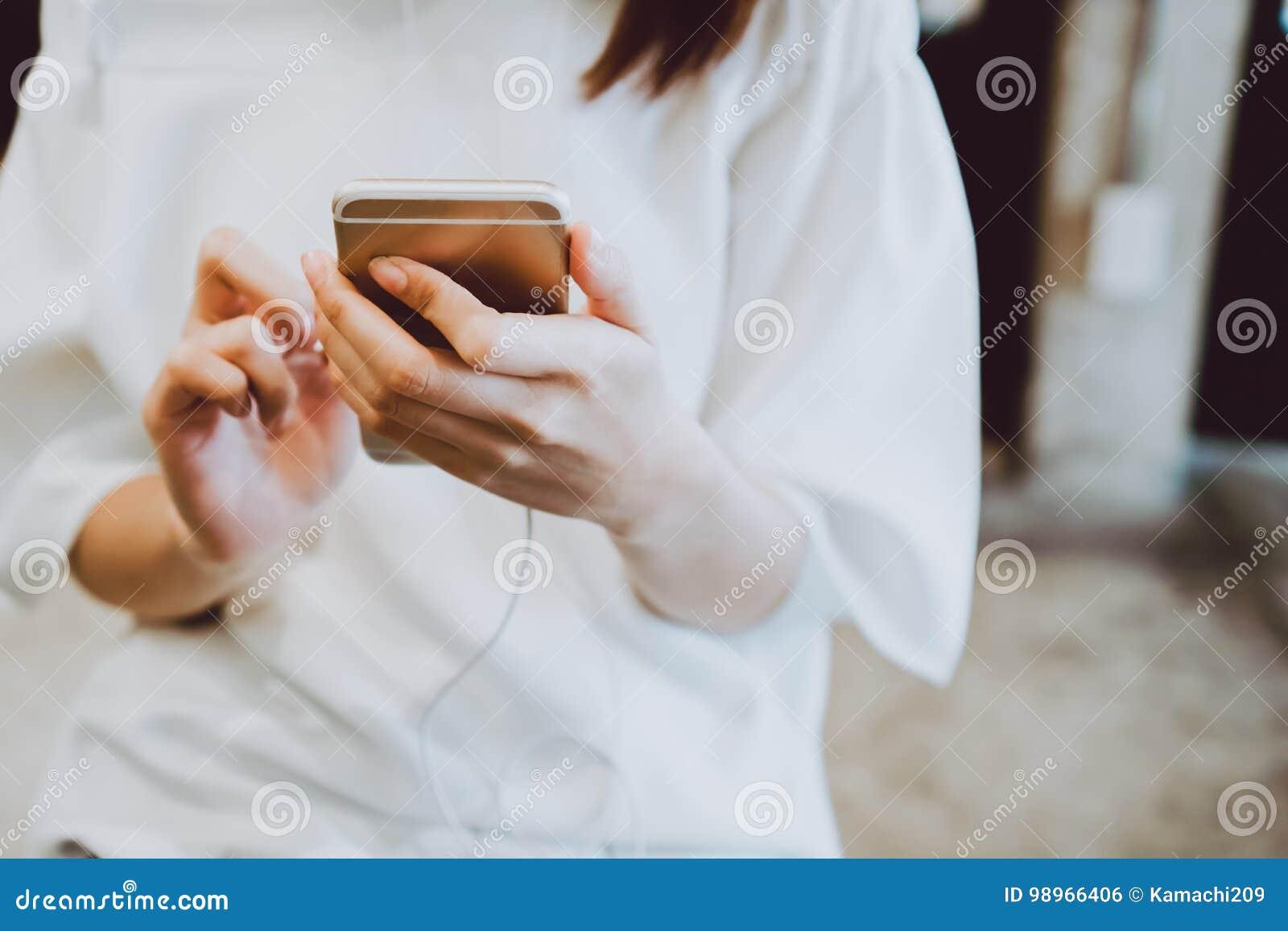 Femmes asiatiques écoutant la musique heureusement avec des écouteurs au téléphone au cours de la journée, détendant des activité