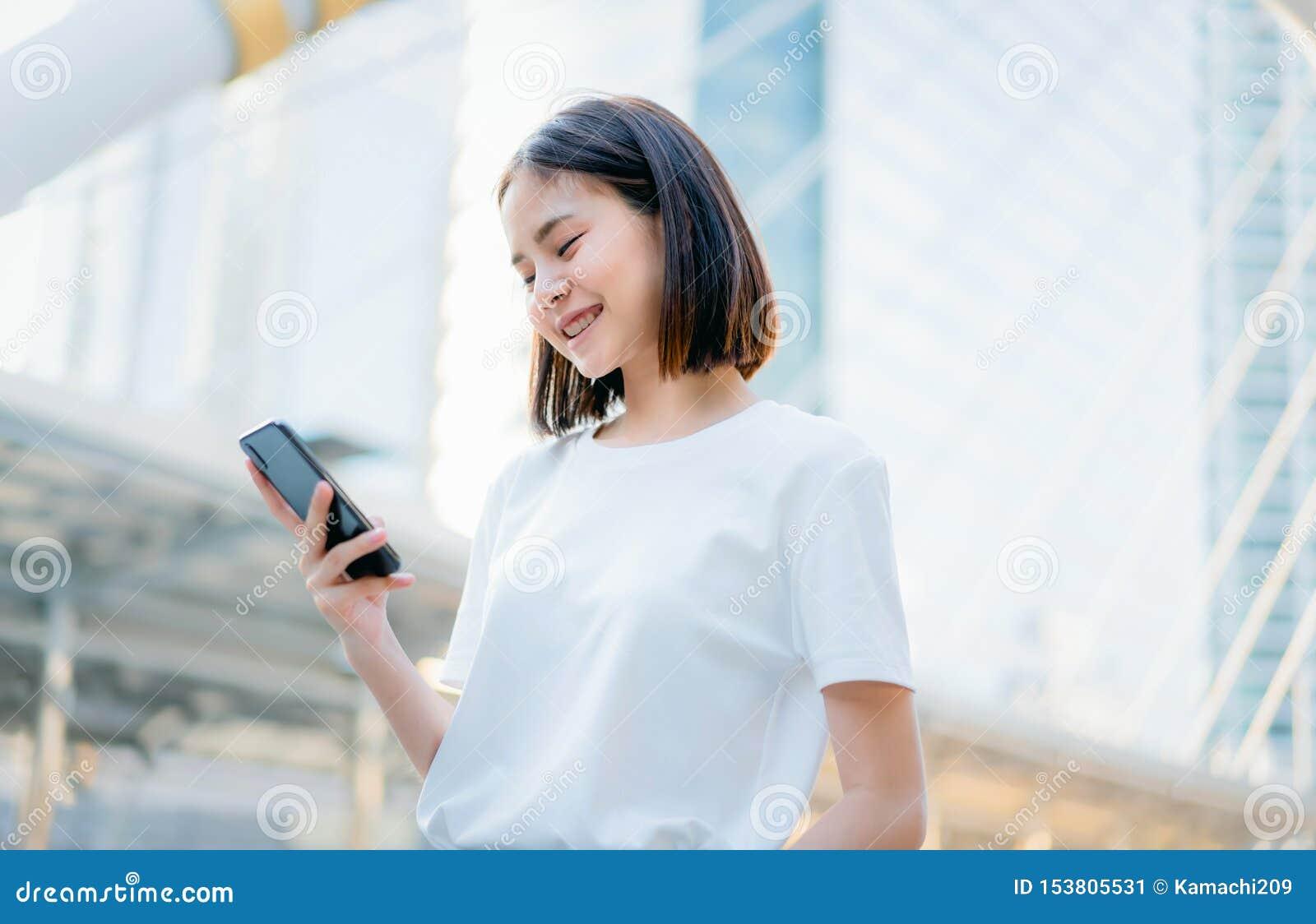 Femmes asiatiques de smartphone de sourire et de utilisation heureux