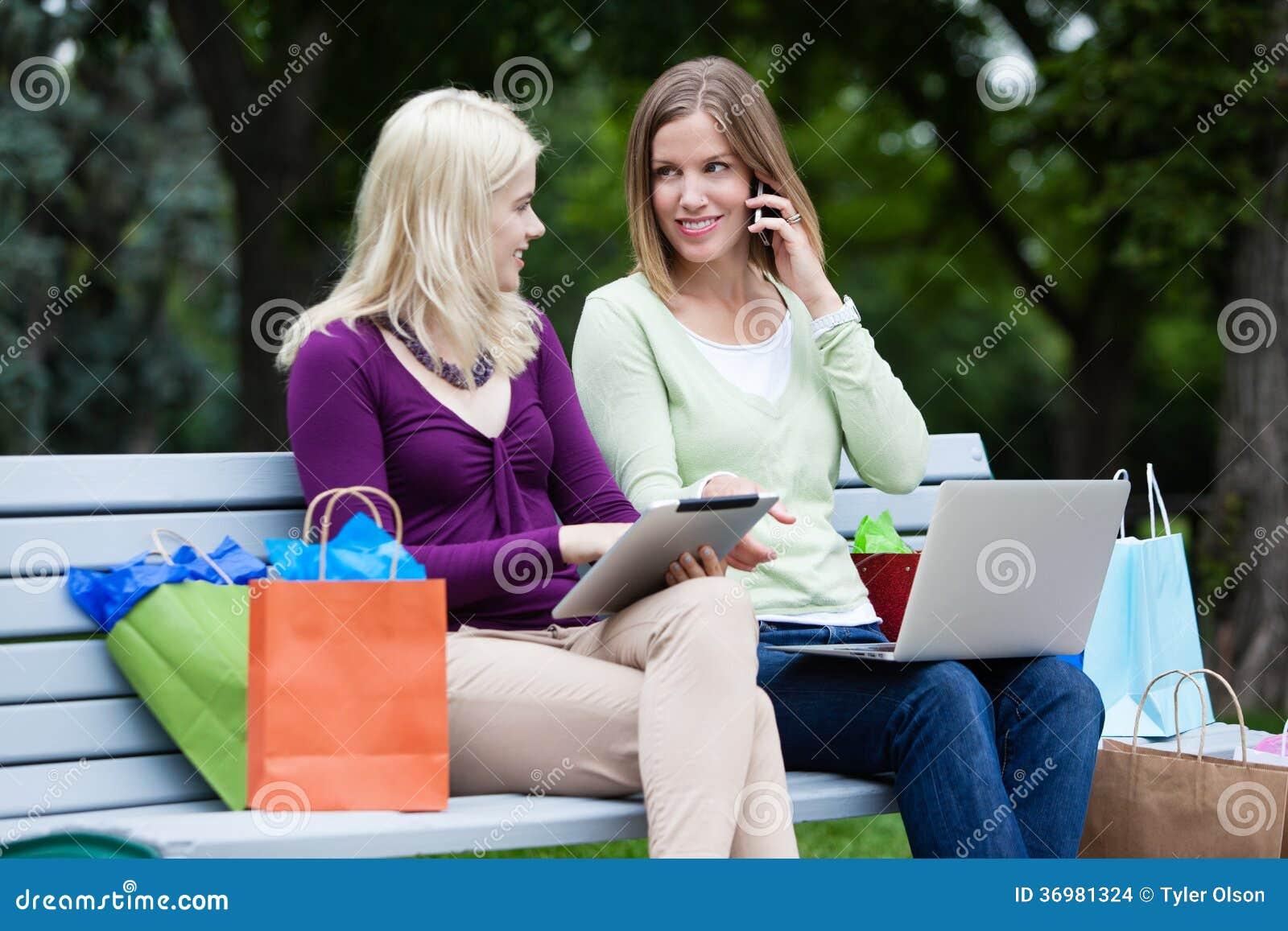 Femmes d achats à l aide de la Tablette et du téléphone portable de Digital