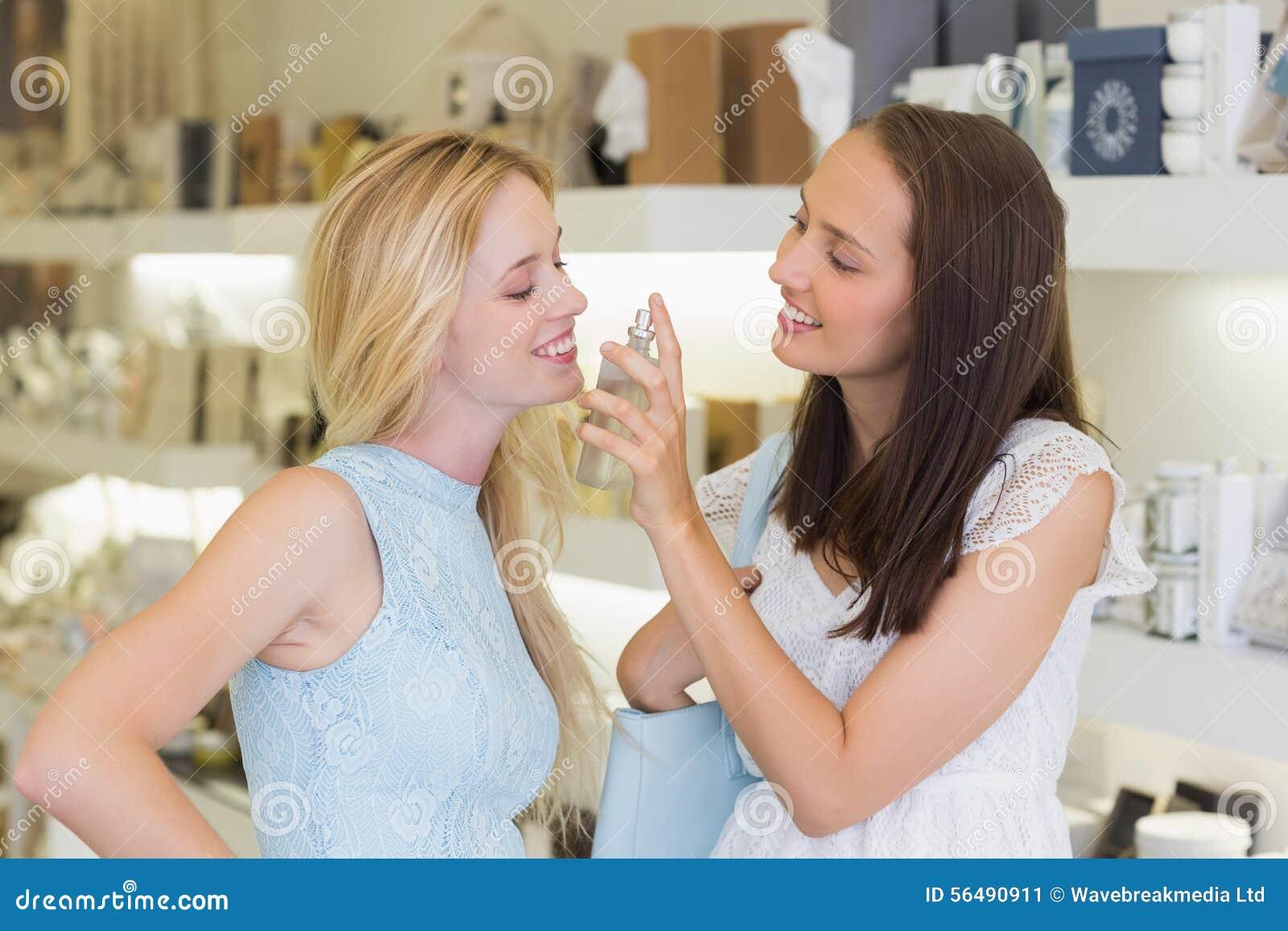Femmes de sourire pulvérisant le parfum
