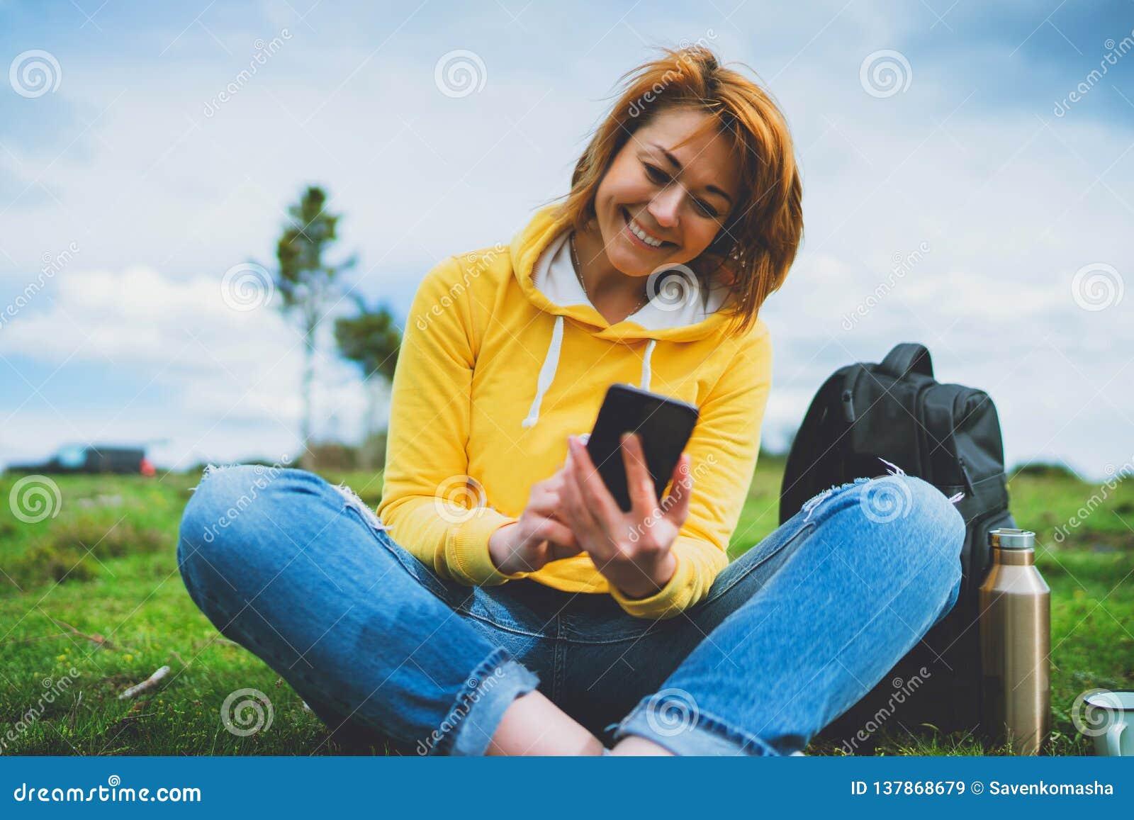 Femmes de sourire se tenant en technologie femelle d instrument de mains, jeune fille de touristes sur l herbe verte de fond util