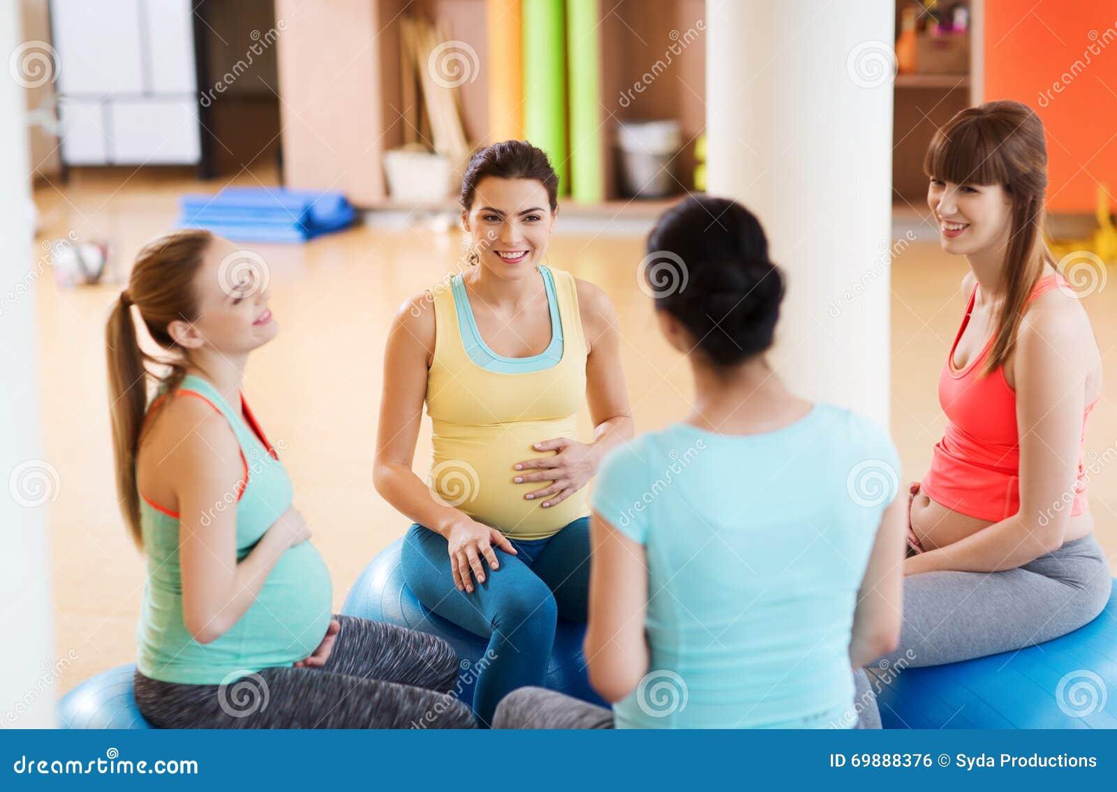 femmes enceintes heureuses s 39 asseyant sur des boules dans le gymnase photo stock image du. Black Bedroom Furniture Sets. Home Design Ideas