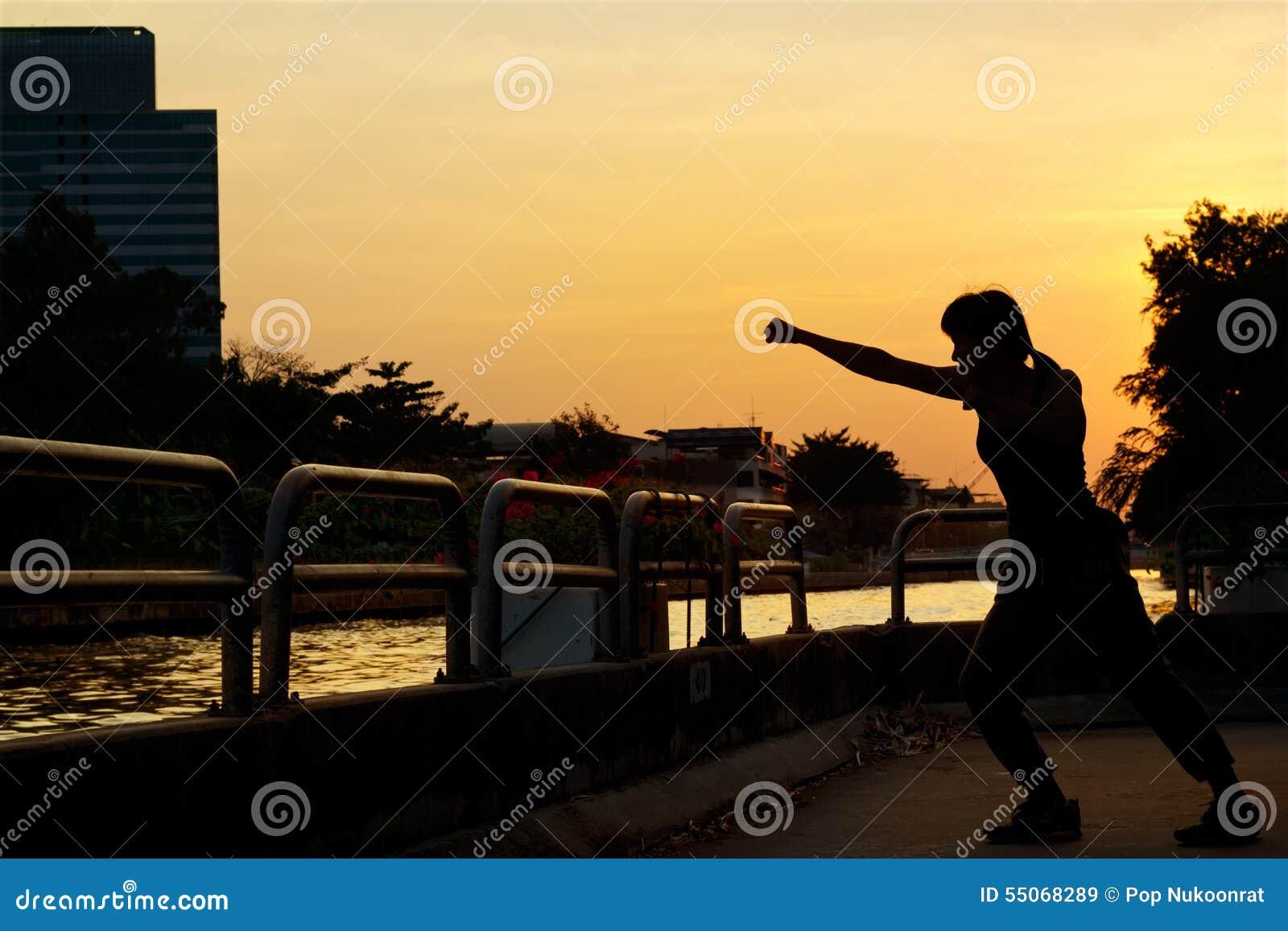 Femmes enfermant dans une boîte la silhouette d exercice et d arts martiaux sur le coucher du soleil