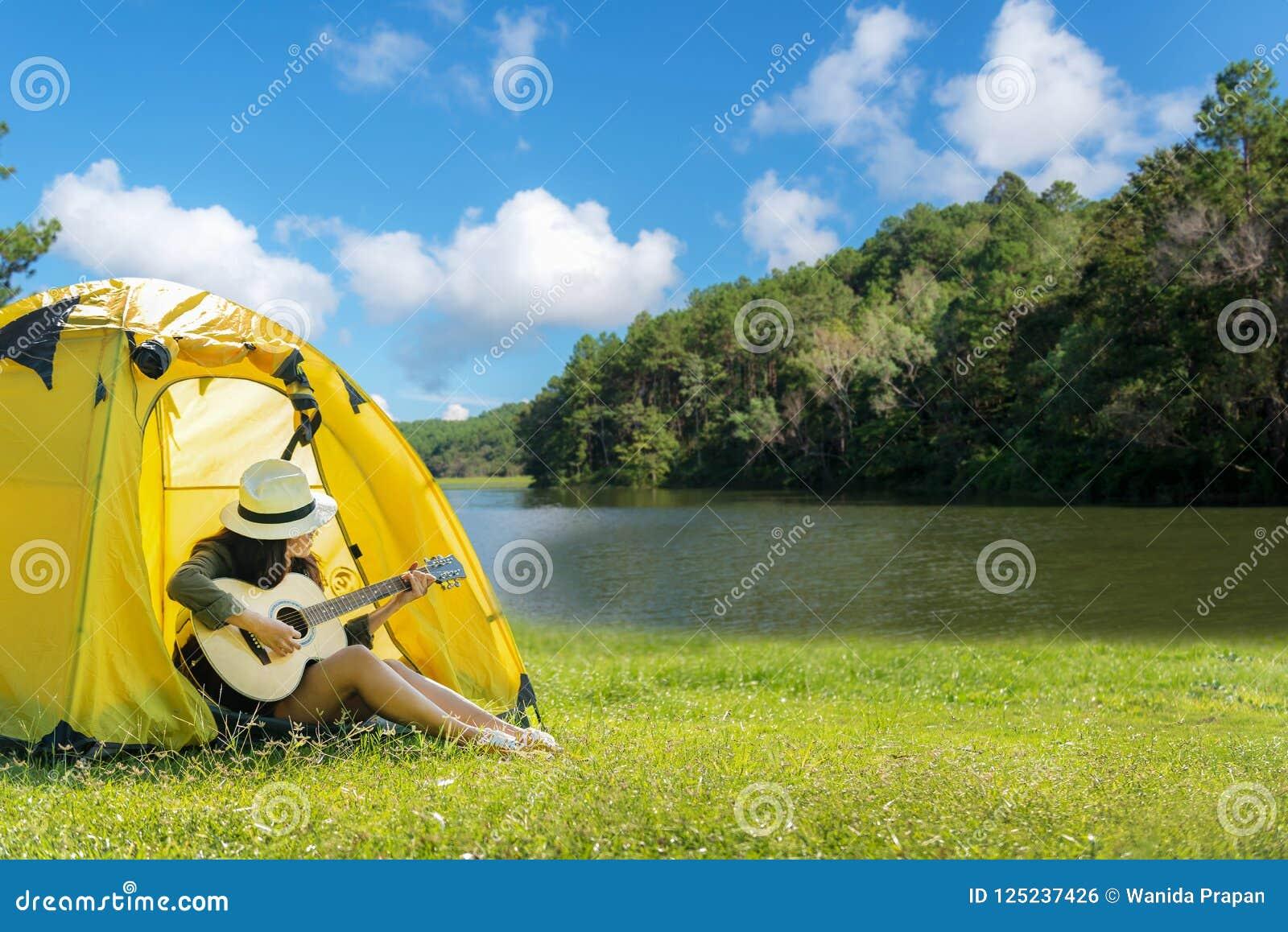 Femmes heureuses de voyageur sur le camping de vacances avec des tentes jouant la guitare dans la forêt près de la rivière