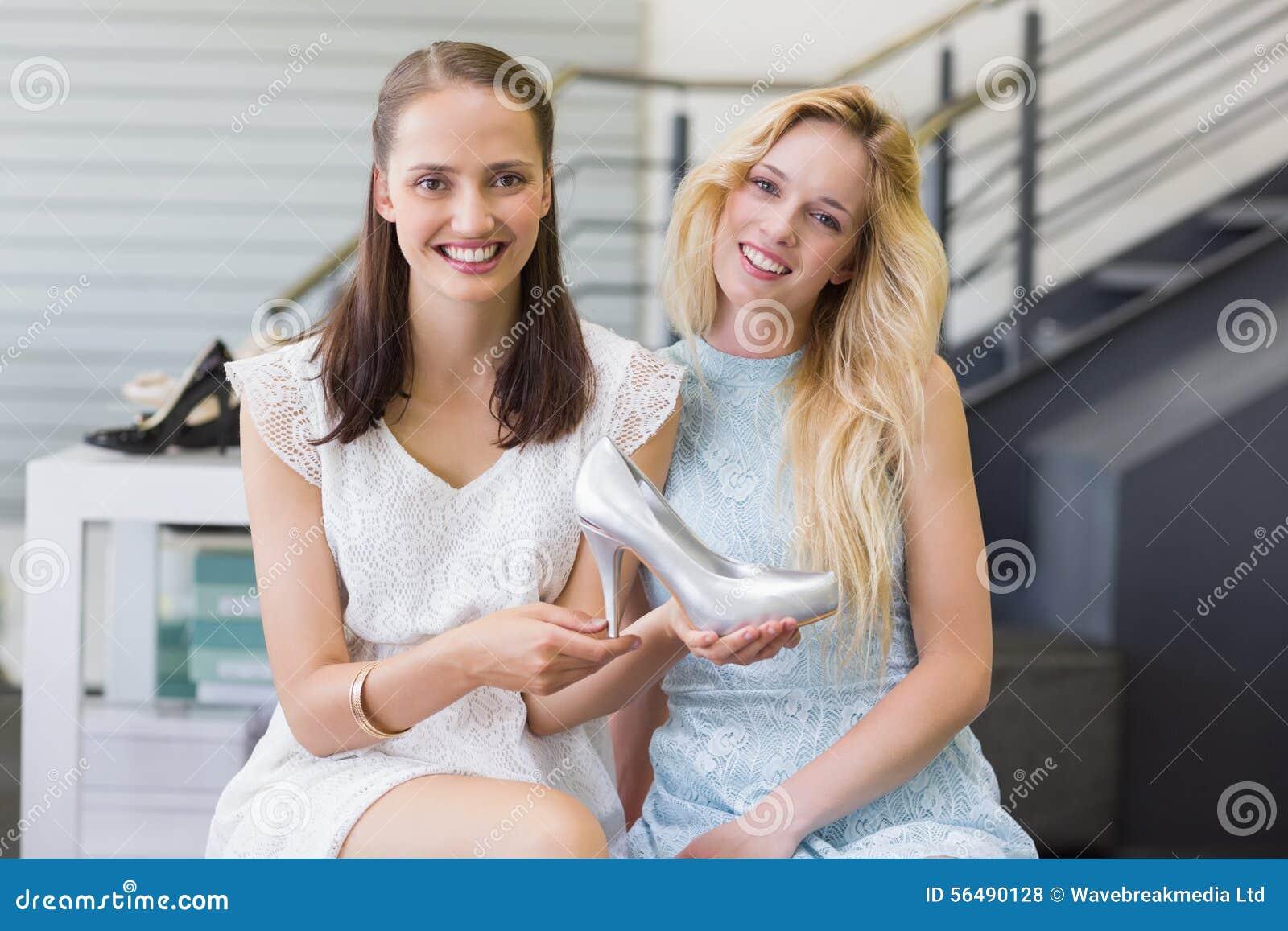 Femmes heureuses souriant à l appareil-photo et montrant des chaussures de talon