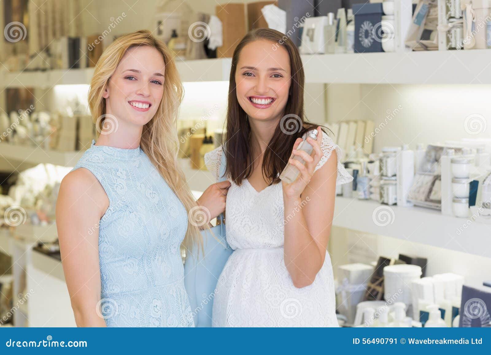 Femmes heureuses souriant à l appareil-photo et tenant la bouteille de parfum